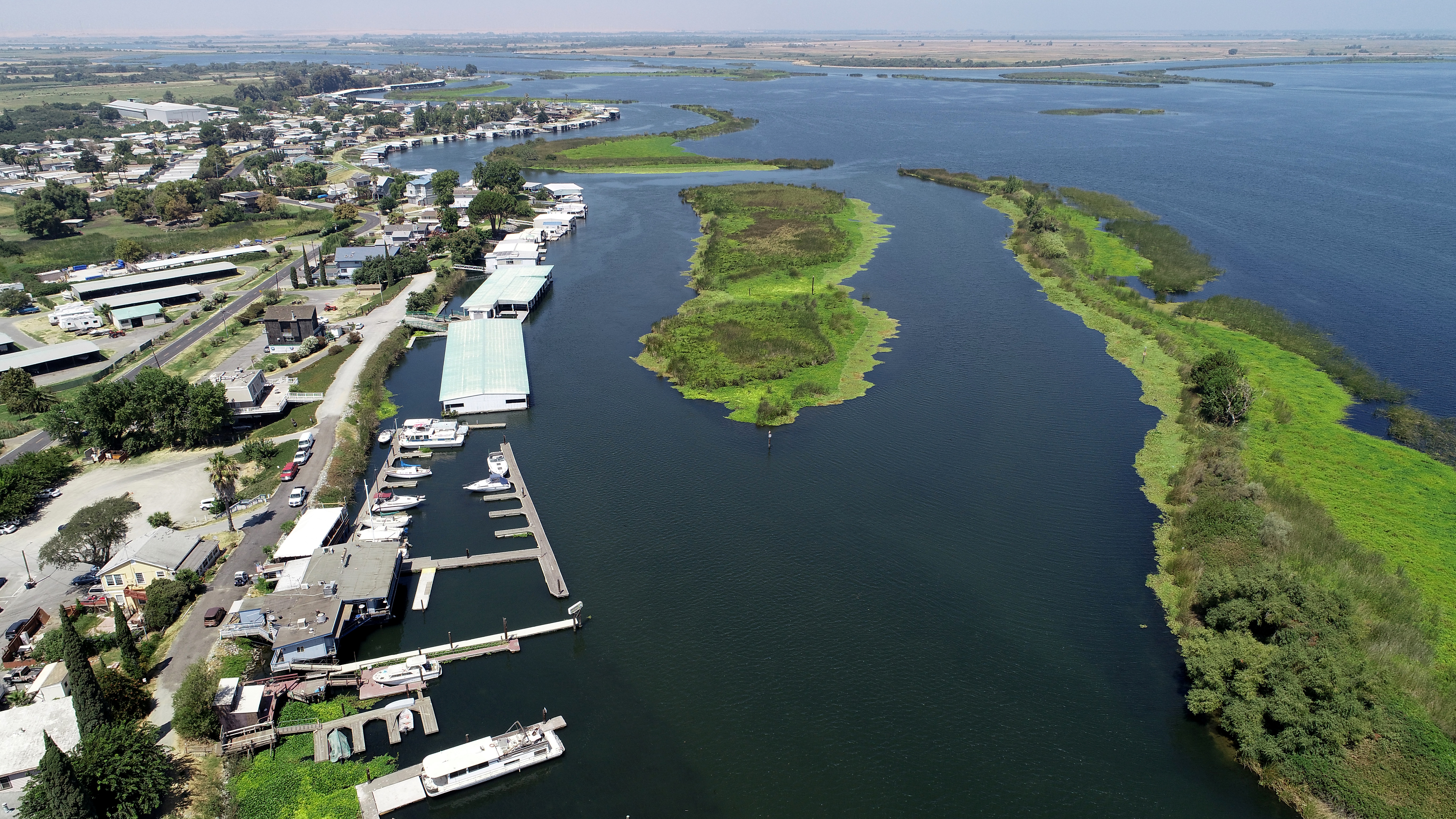 A marina photographed from the air, with white buildings on the left and green, verdant sandbars on the right.