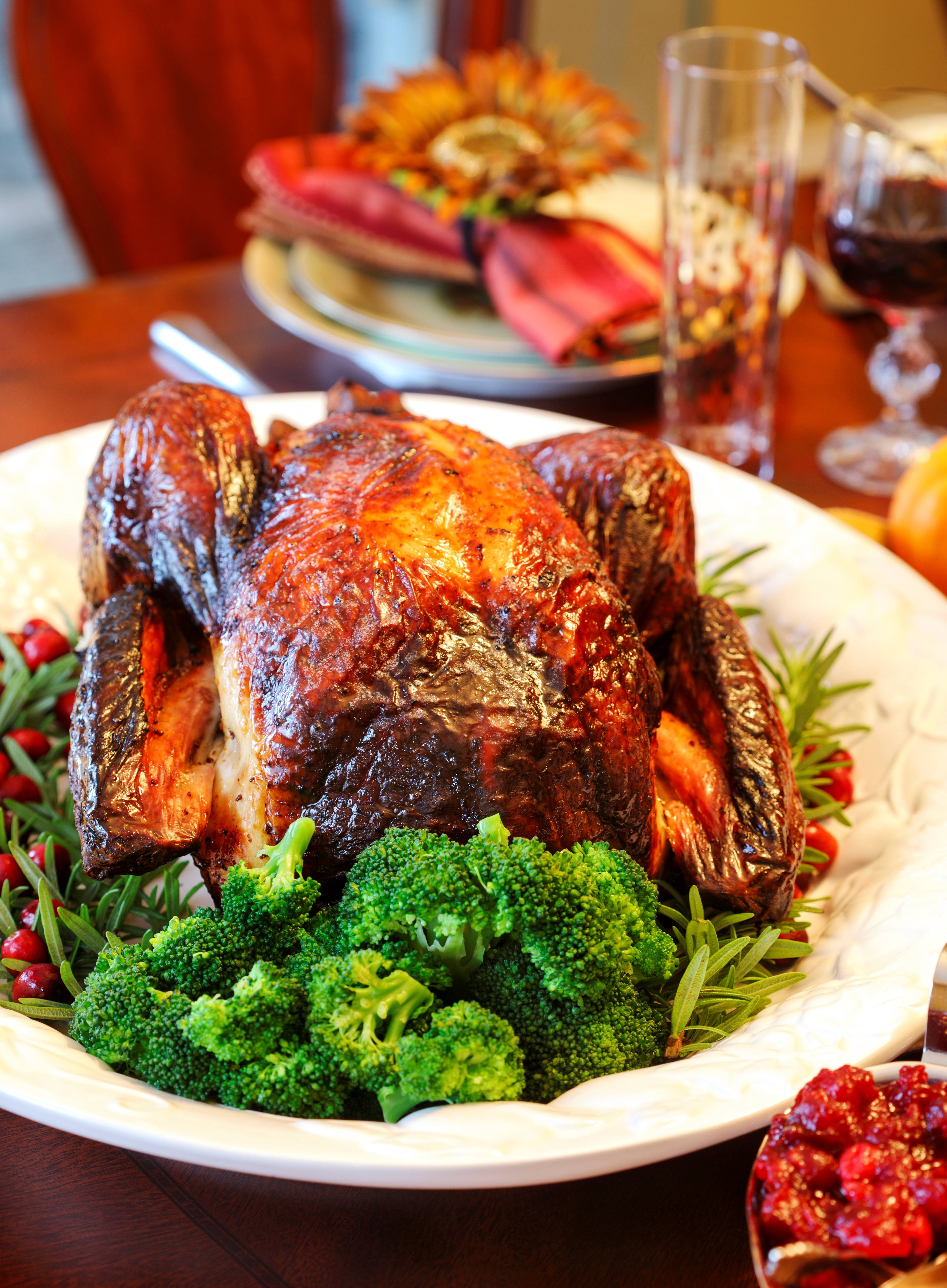 A photo of a Thanksgiving turkey on a table with broccoli and other vegetables