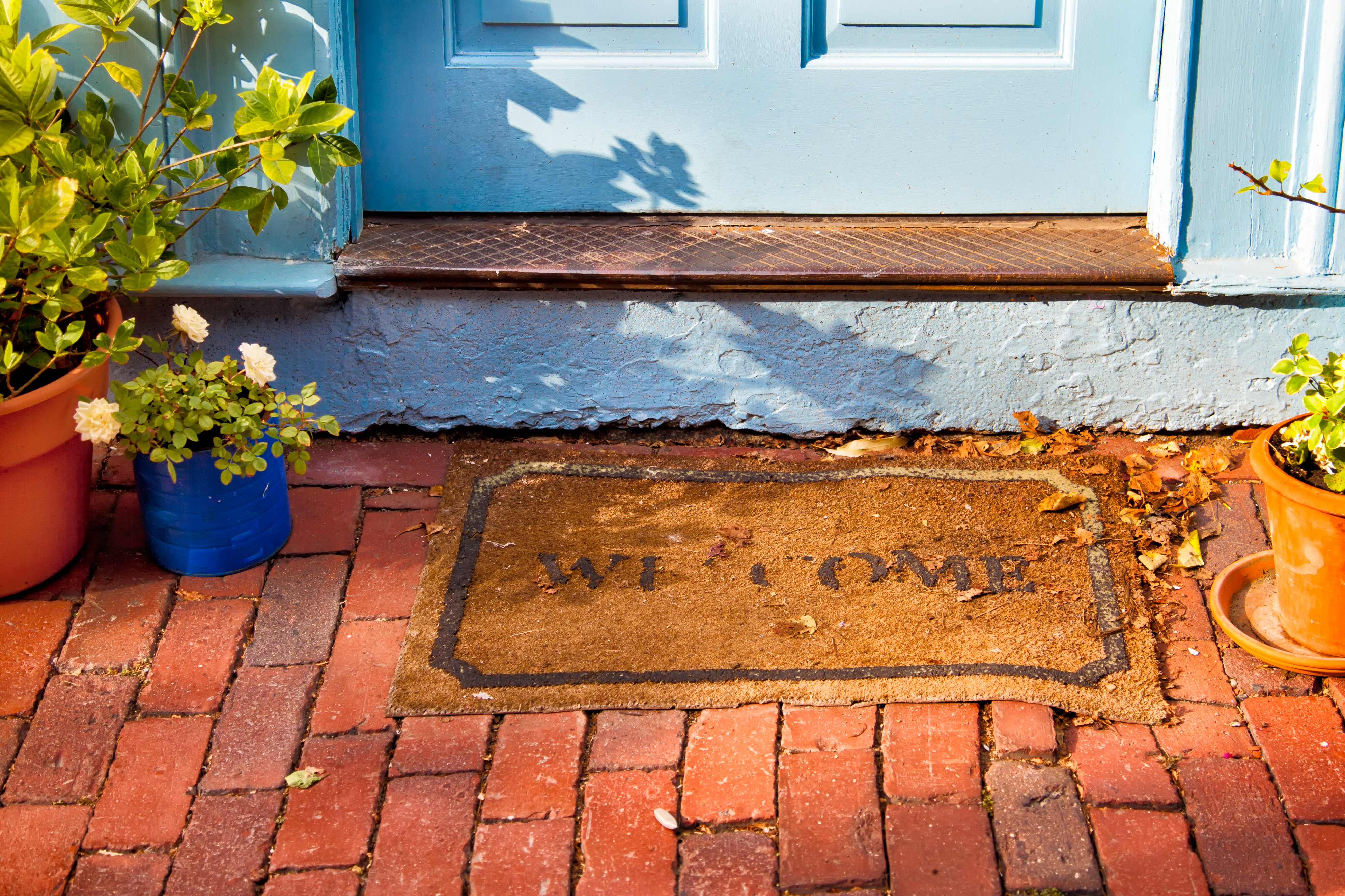 A welcome mat at the outside foot of a door on a brick path.