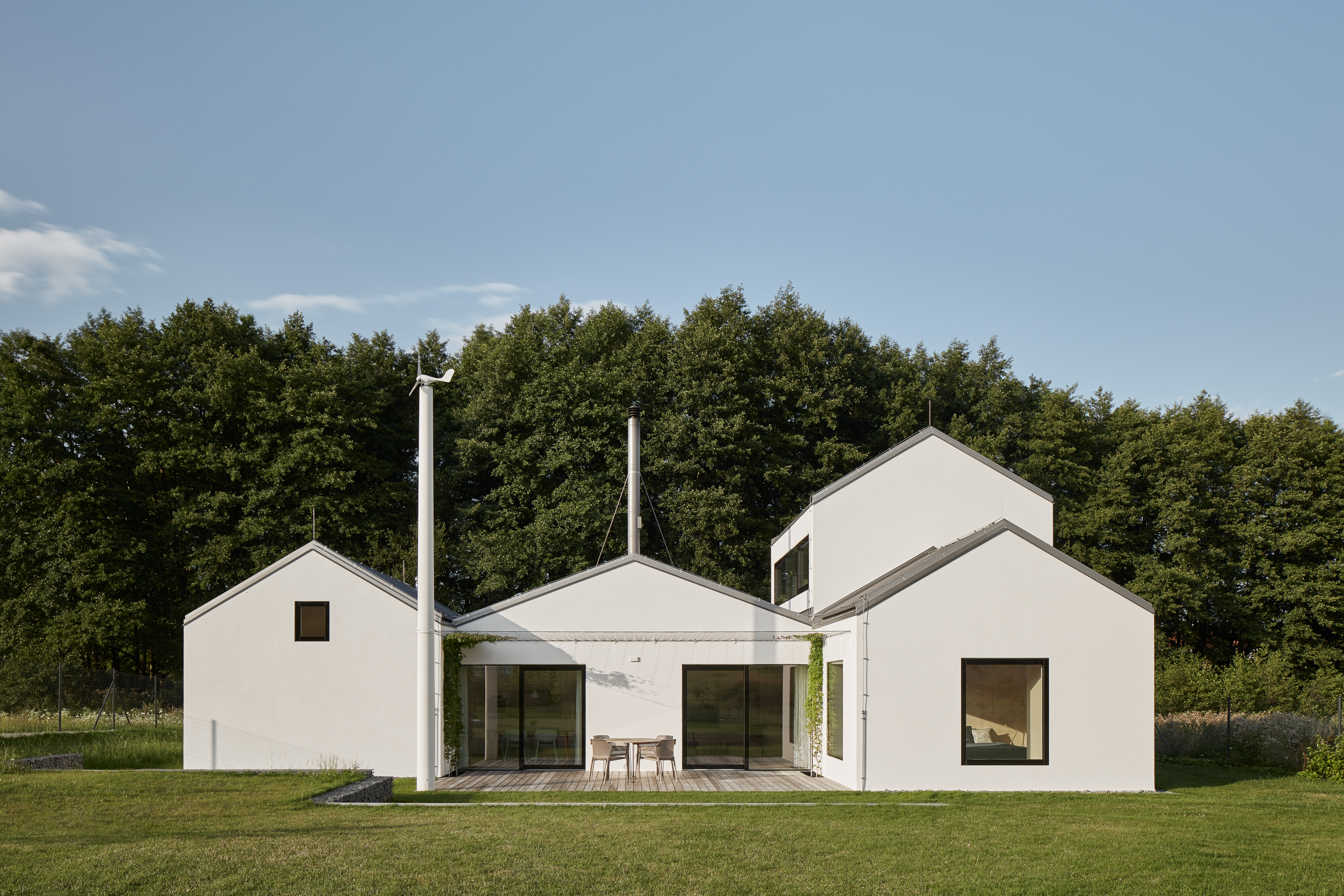 A geometric white house sits on a rolling green lawn with tall trees in the background and a blue sky.