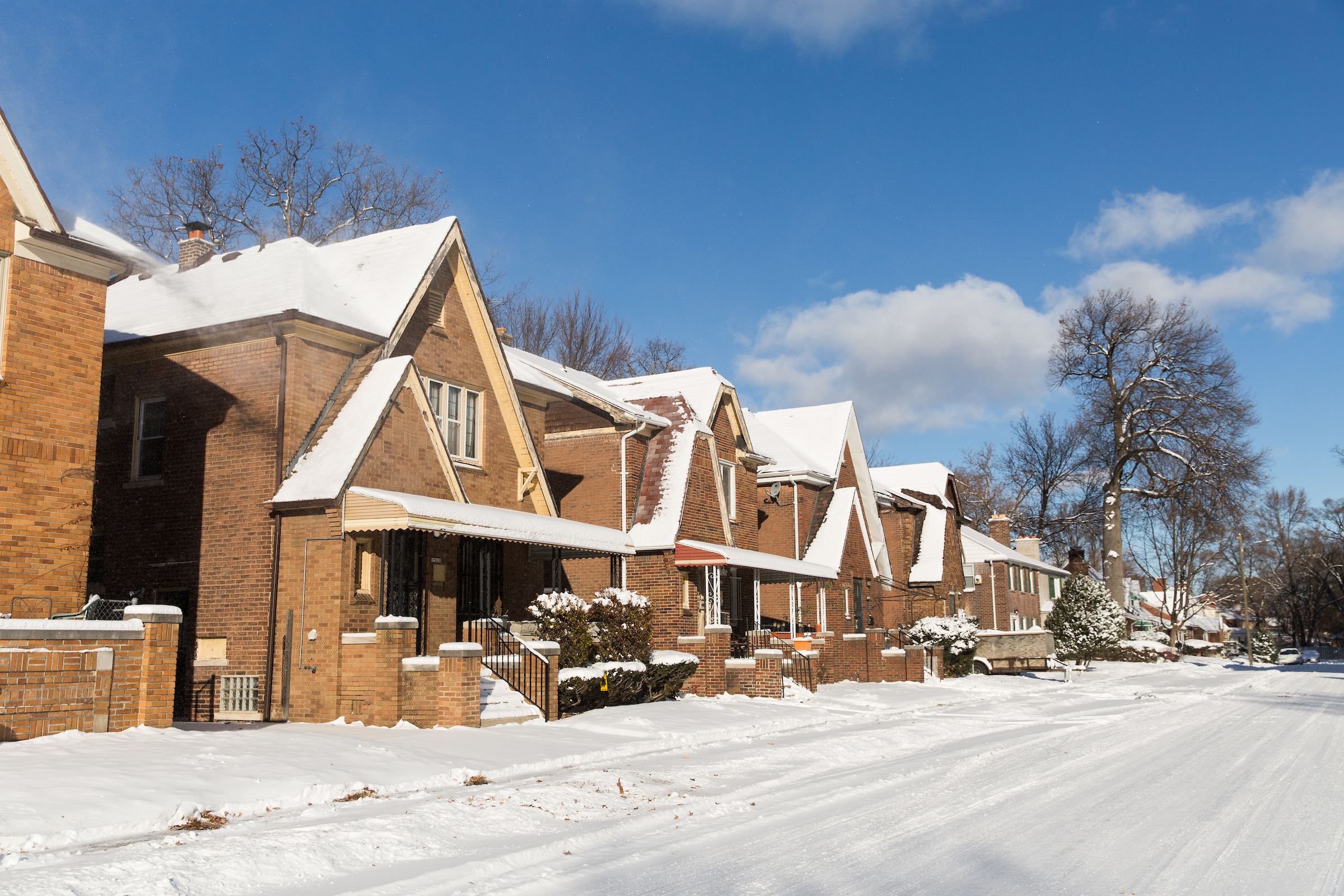 A row of snow-covered brick homes.