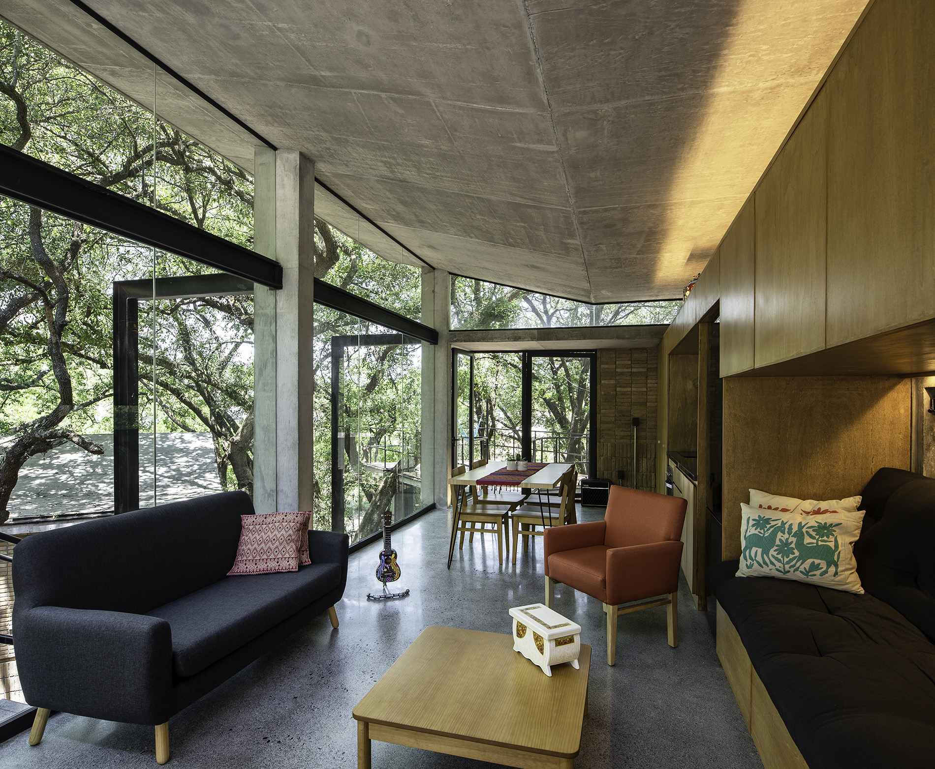 Modern couch and arm chairs in a treehouse-style living room with large windows.