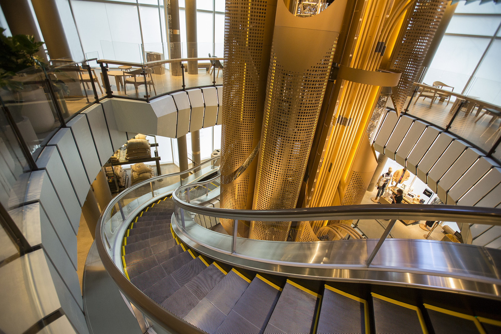 Large brass tubes filled with coffee beans and surrounded by a circular escalator.