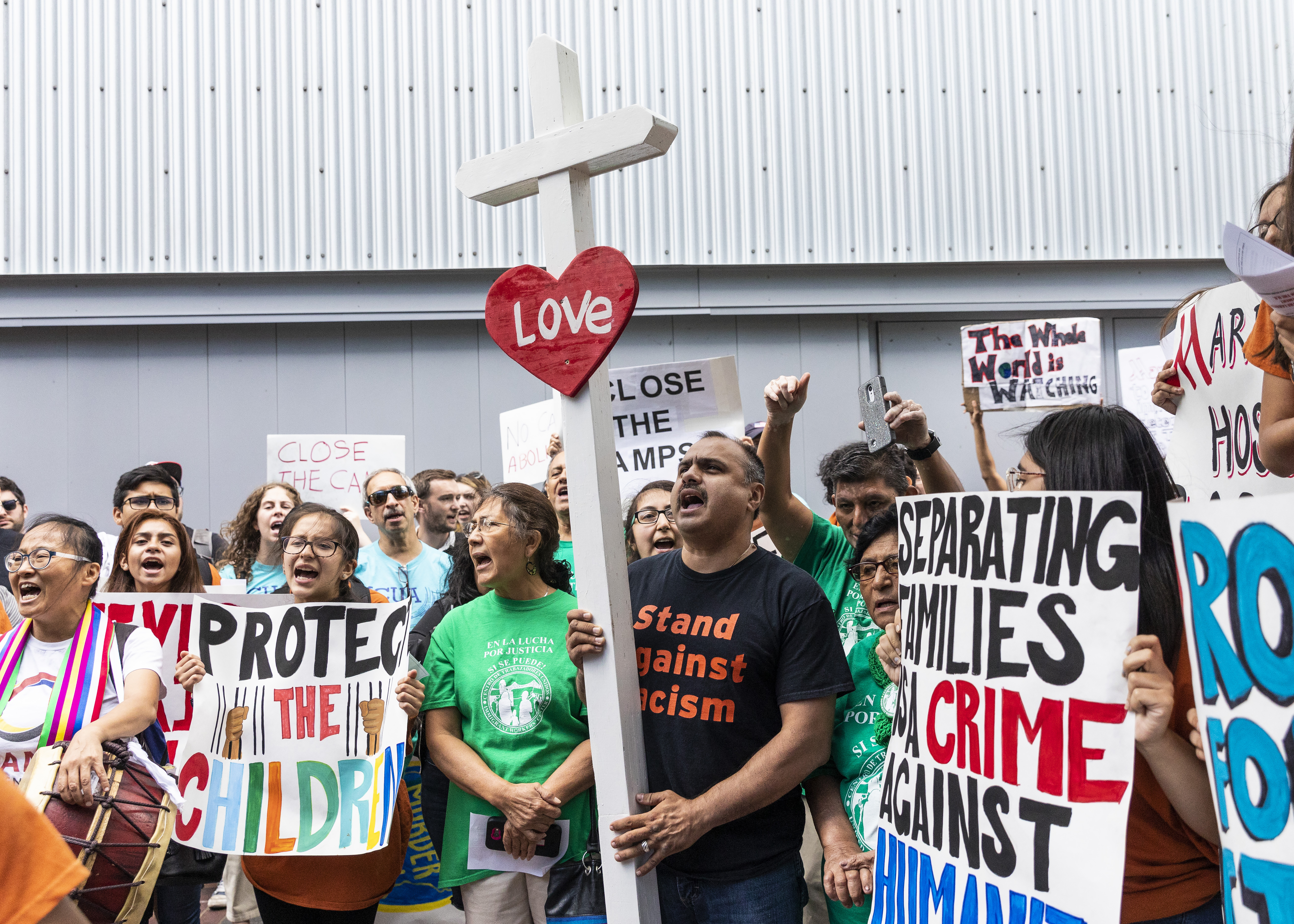 Casildo Cuevas (center, holding the cross) joins dozens of other immigrant rights activists to protest outside the Marriott Marquis Chicago in July 2019.