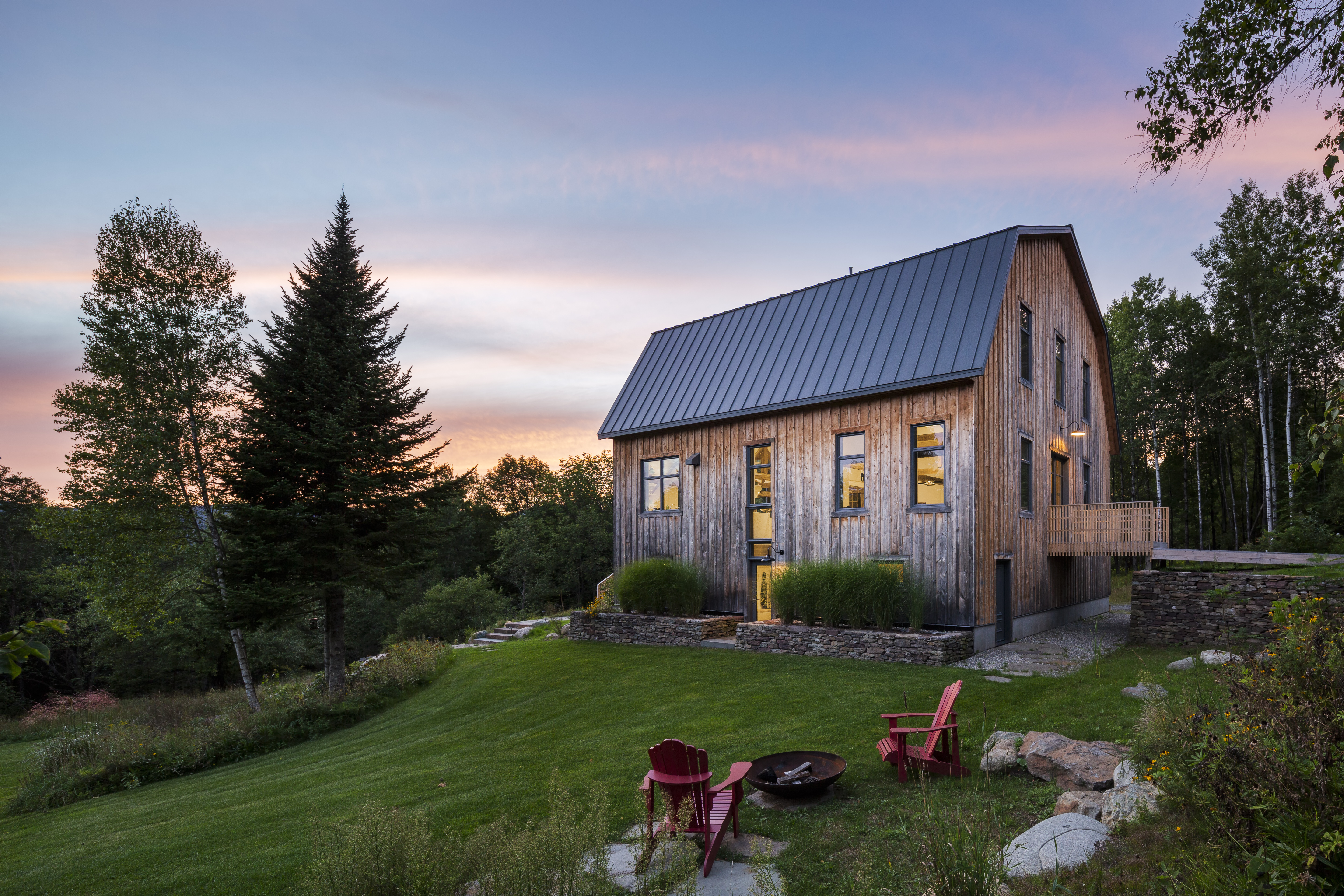 A restored barn sits on a grassy plot of land at sunset. There are large pine trees and red Adirondack chairs.