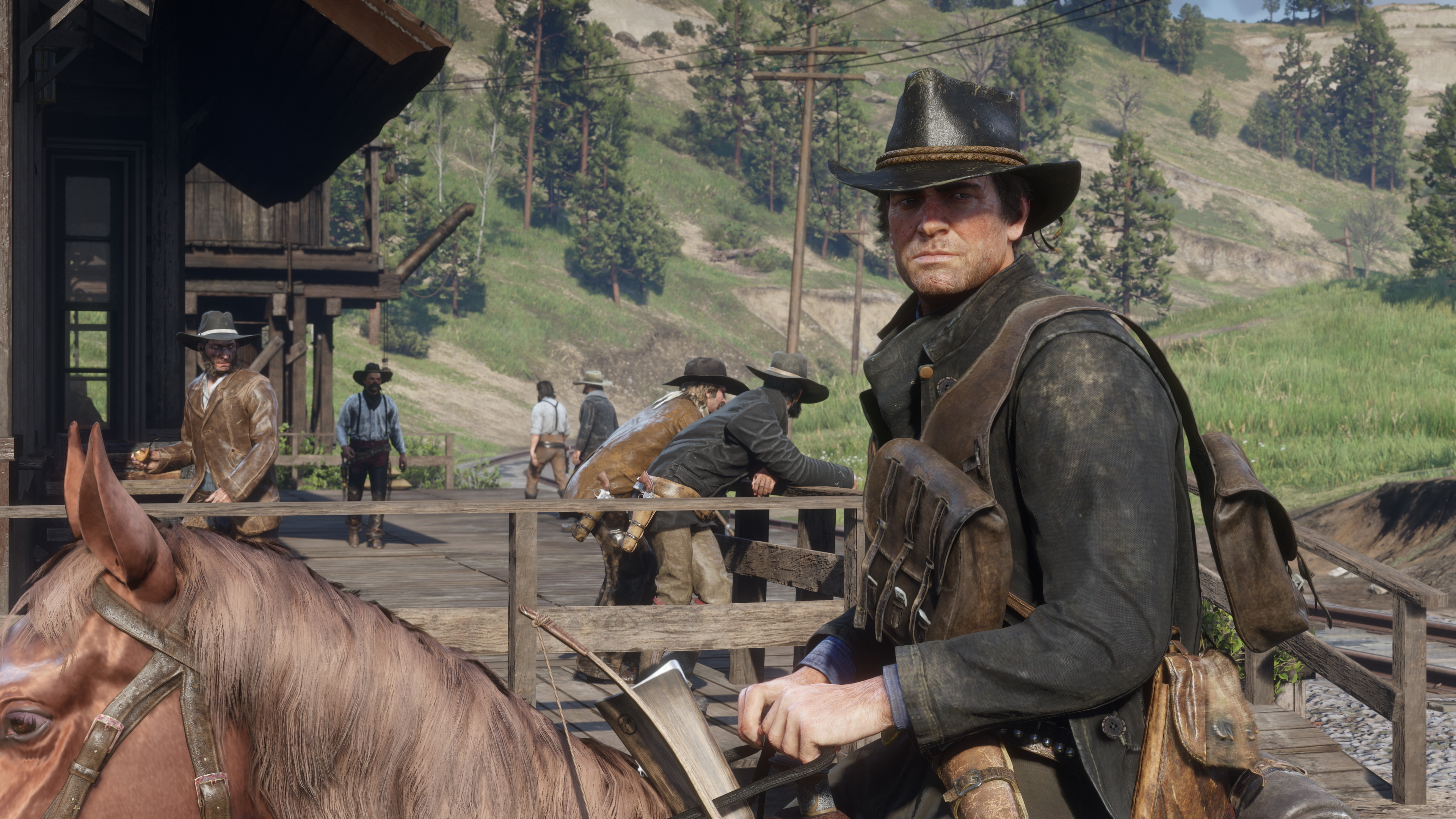 a man in a cowboy hat, Arthur Morgan, sitting on horseback riding past a wooden train platform in Red Dead Redemption 2
