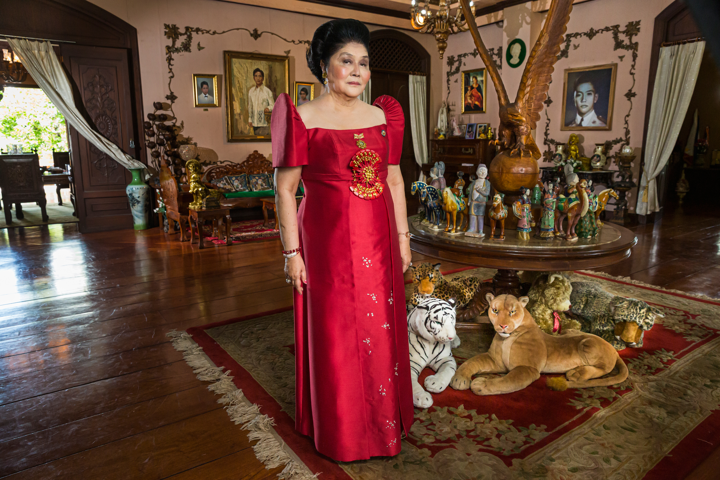 Imelda Marcos wearing a formal gown and standing inside her residence.