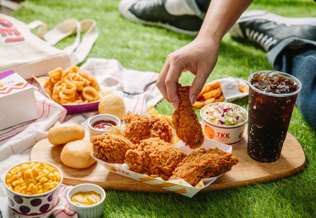 Fried chicken, corn, cole slaw, soda, and curly fries on a picnic board