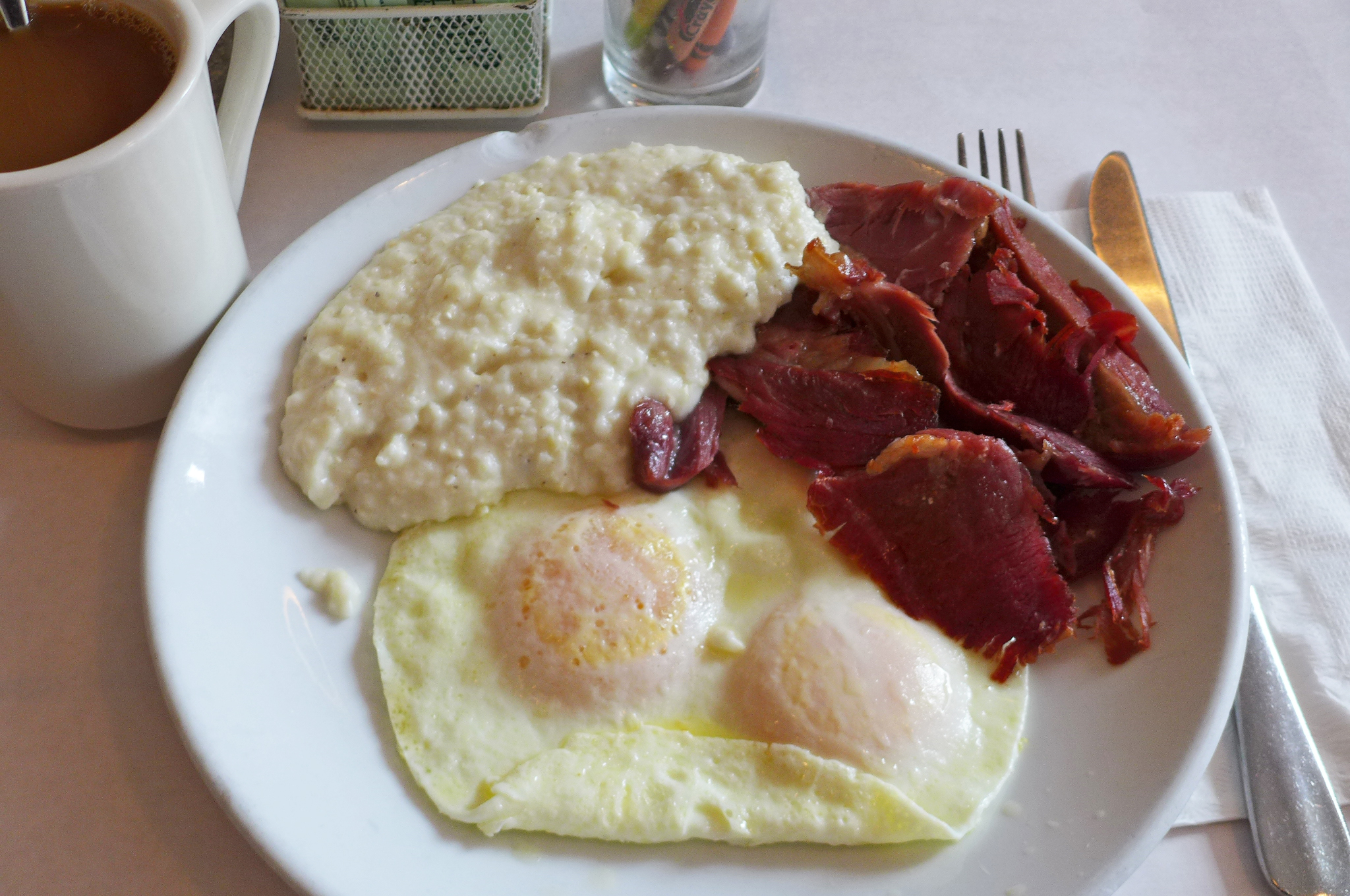 Two over easy eggs, a pool of lumpy grits, and pile of country ham hacked off in swatches rather than slices.