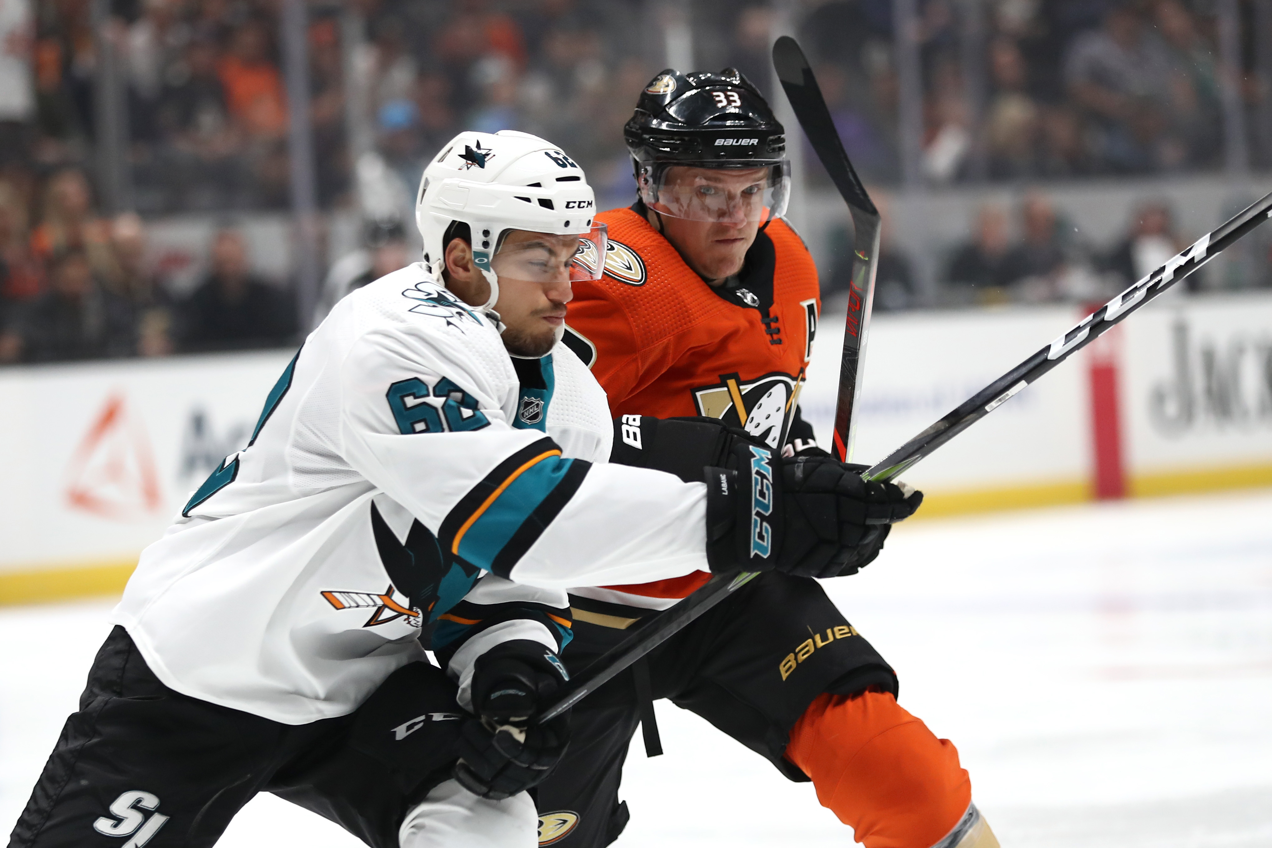 ANAHEIM, CALIFORNIA - OCTOBER 05: Kevin Labanc #62 of the San Jose Sharks battles Jakob Silfverberg #33 of the Anaheim Ducks for position during the first period of a game at Honda Center on October 05, 2019 in Anaheim, California.