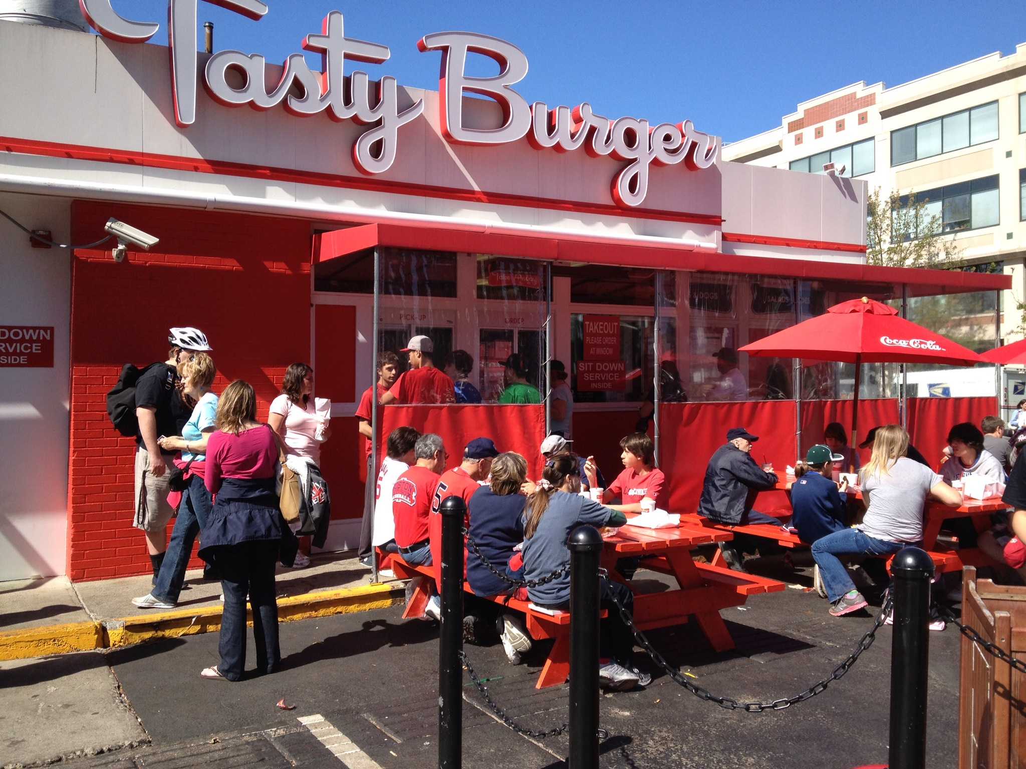 People gather on the patio at Tasty Burger Fenway, which boasts a bright red and white exterior