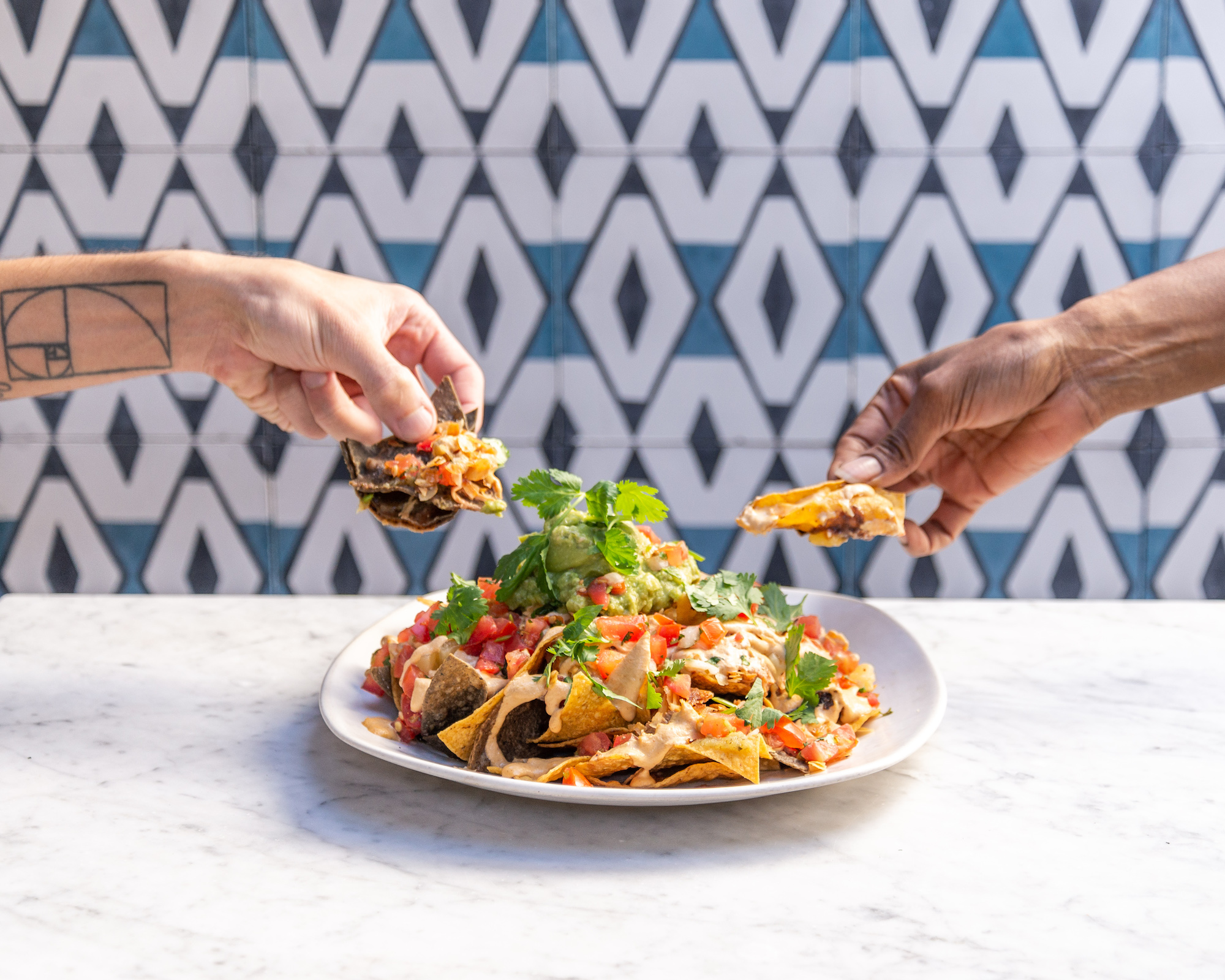 Vegan nachos getting pulled in two directions on a plate.