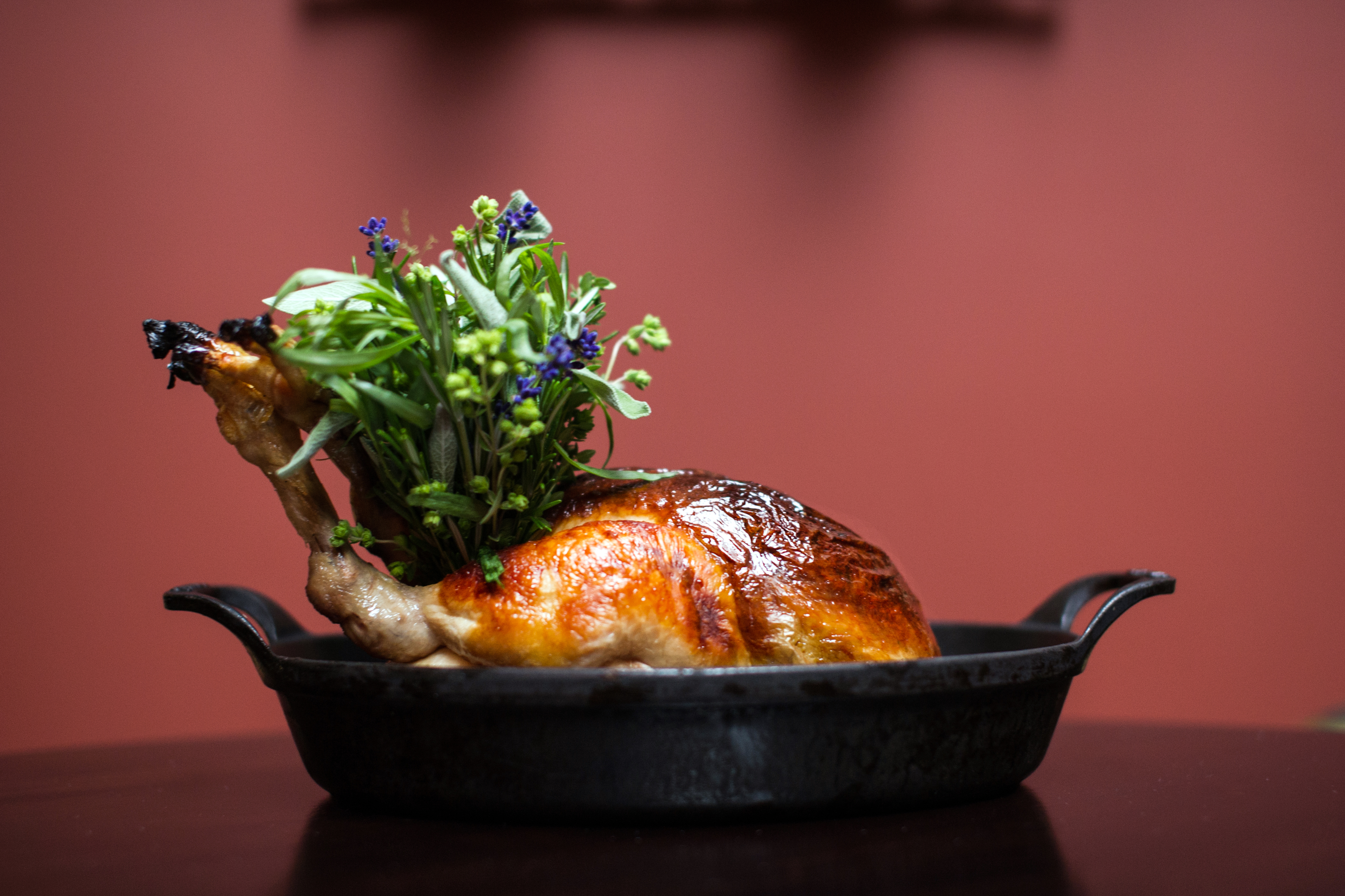 Roast chicken in a black dish on a red background