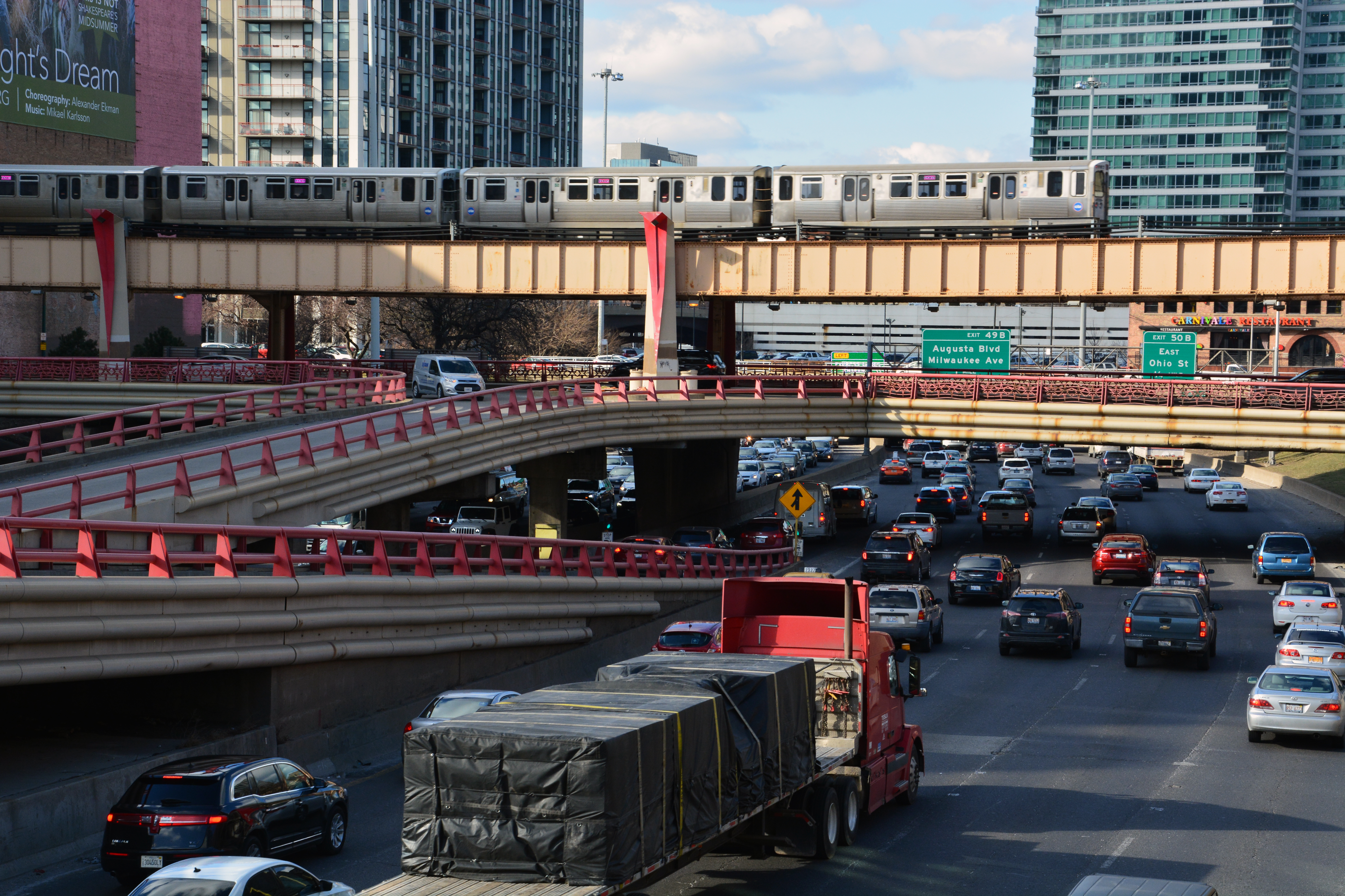 A view of expressway ramps and traffic on the road. There is an L train passing over the roads.