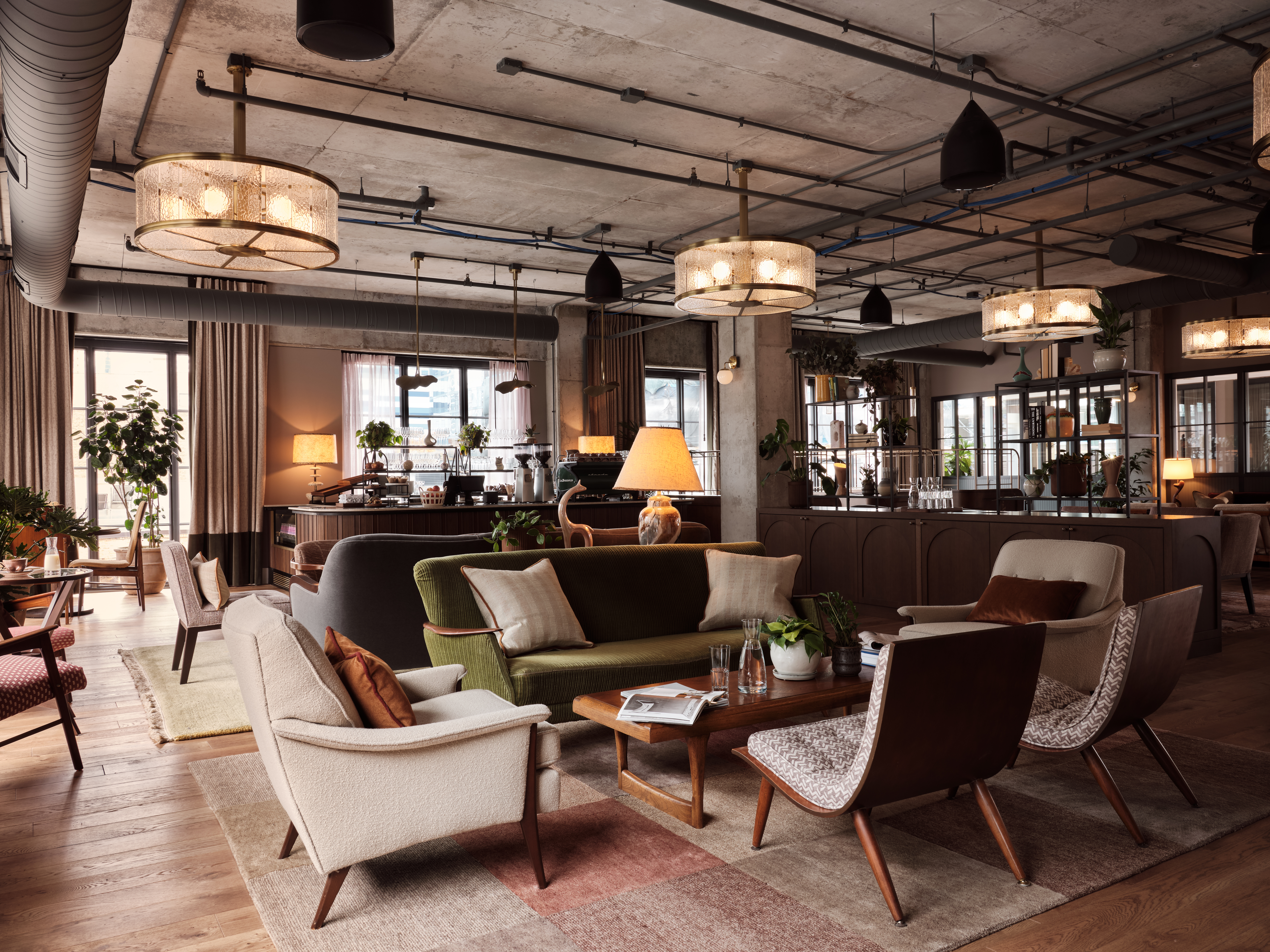 A large room with a concrete ceiling, comfortable couches, chairs and coffee tables.
