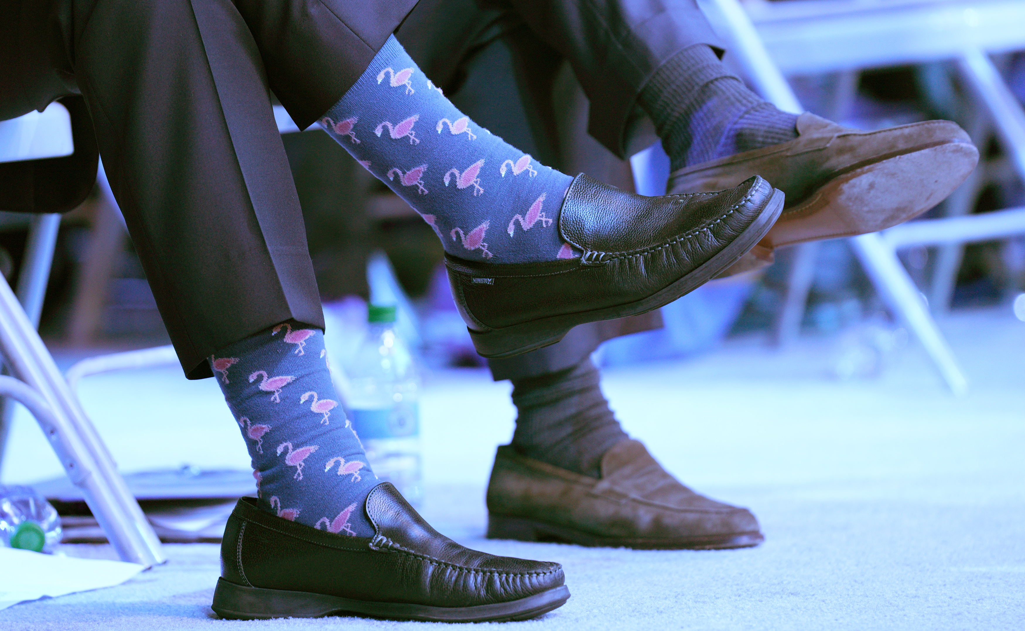 Men's feet in loafers with colorful socks.