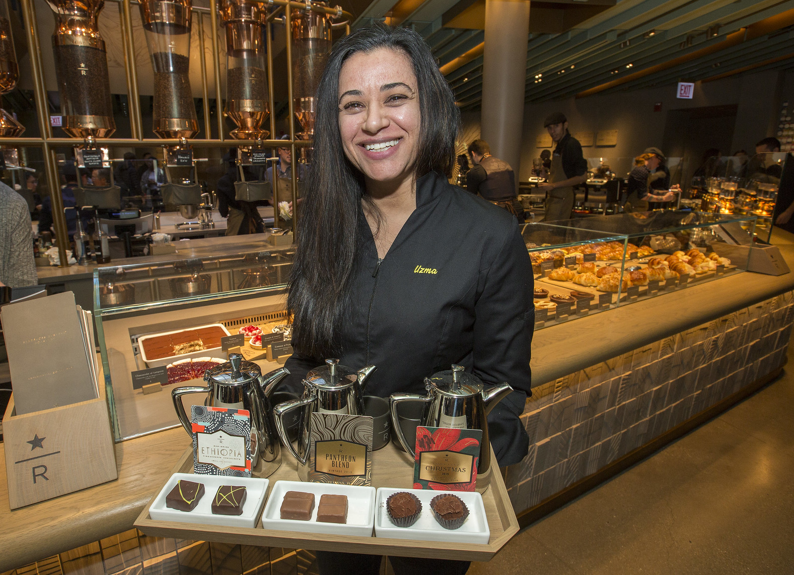 A woman holding a tray of truffles and coffee pots.