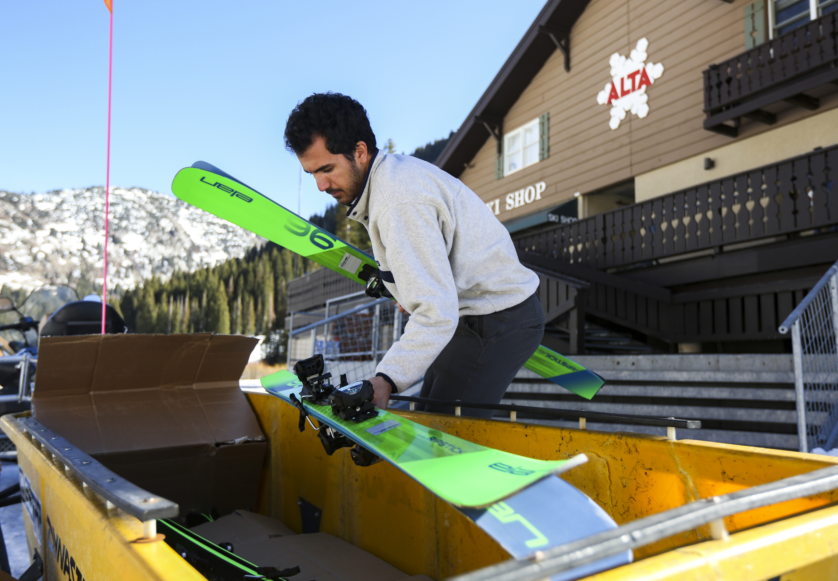 Fayik Abdi unloads pairs of skis from a bin as he and another worker transfer items between Alta rental shops in preparation for the ski season at Alta Ski Resort in Little Cottonwood Canyon on Monday, Nov. 11, 2019. This is Abdi's first day working for Alta after two seasons working for Snowbird just down the canyon.