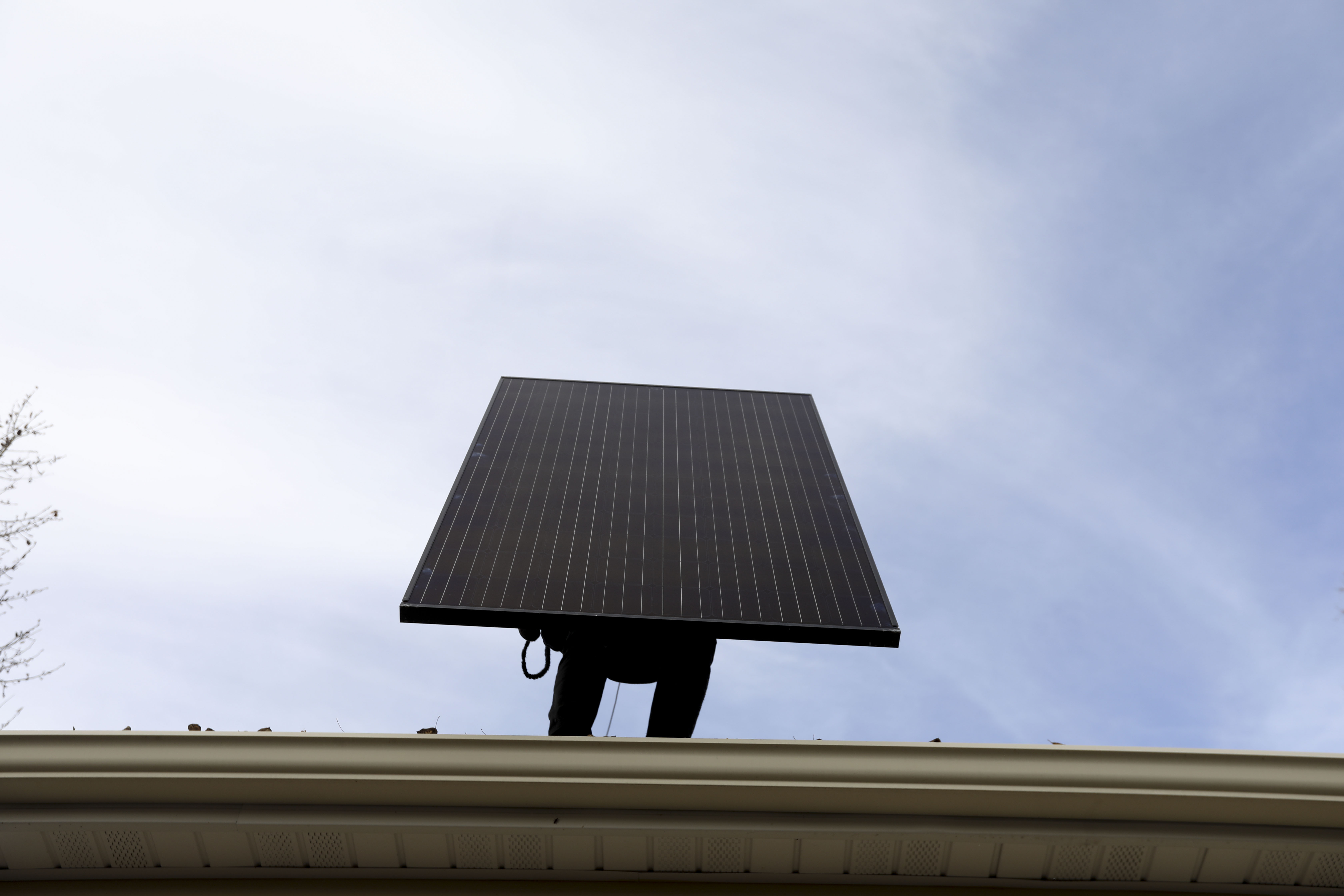 Dom Ontiveros, of Auric Energy, lifts a solar panel onto the roof of the 1,000th home that utilized the Empower SLC Solar program in Salt Lake City on Thursday, Nov. 14, 2019. Empower SLC Solar, a community-led program in Salt Lake County, helps residents overcome the logistical and financial hurdles of going solar.