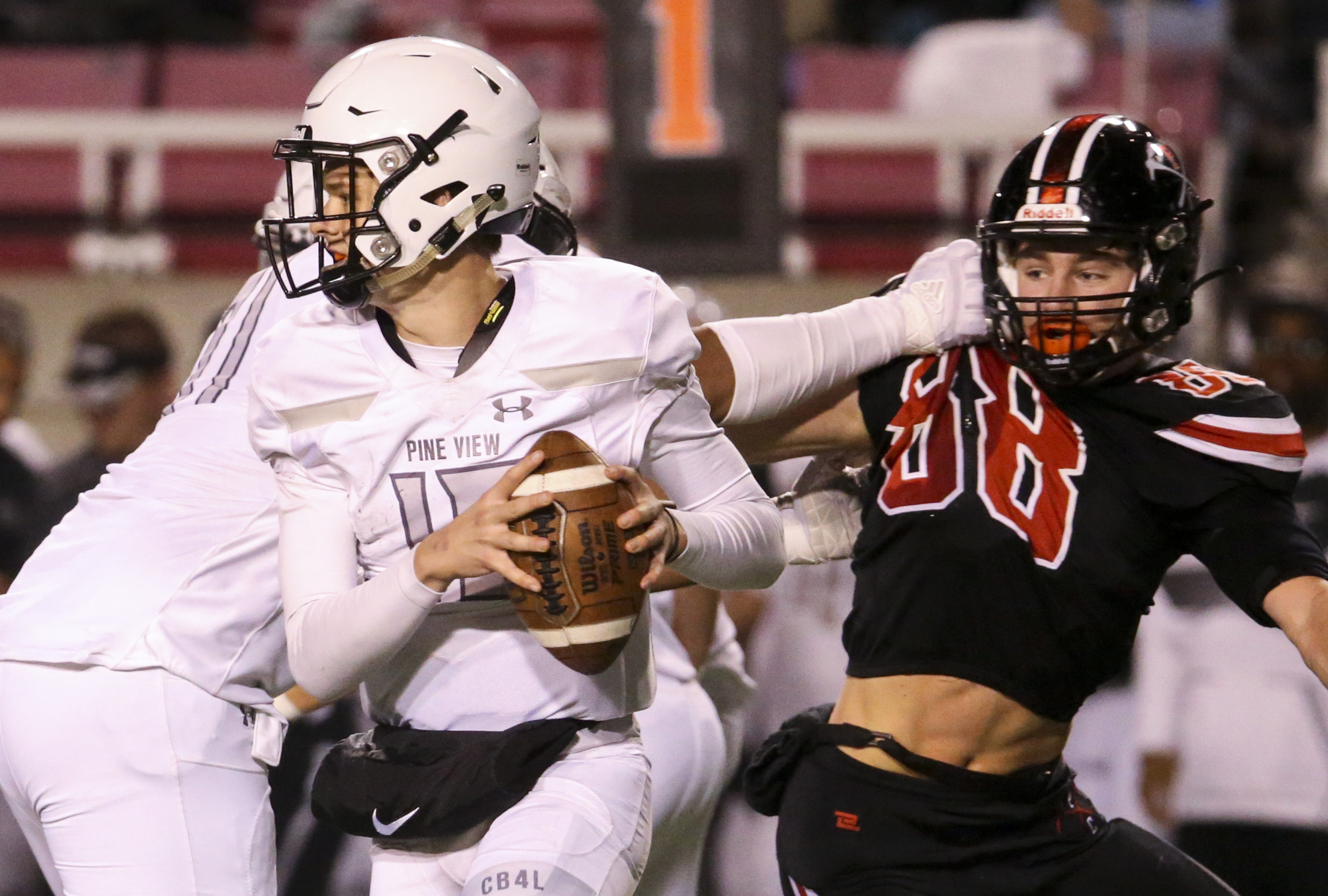Pine View quarterback Macloud Crowton (15) looks for a throw downfield while receiving a block against Park City safety Andrew Pederson (88) during the second half of a 4A semifinals high school football game at Rice-Eccles Stadium in Salt Lake City on Thursday, Nov. 14, 2019.