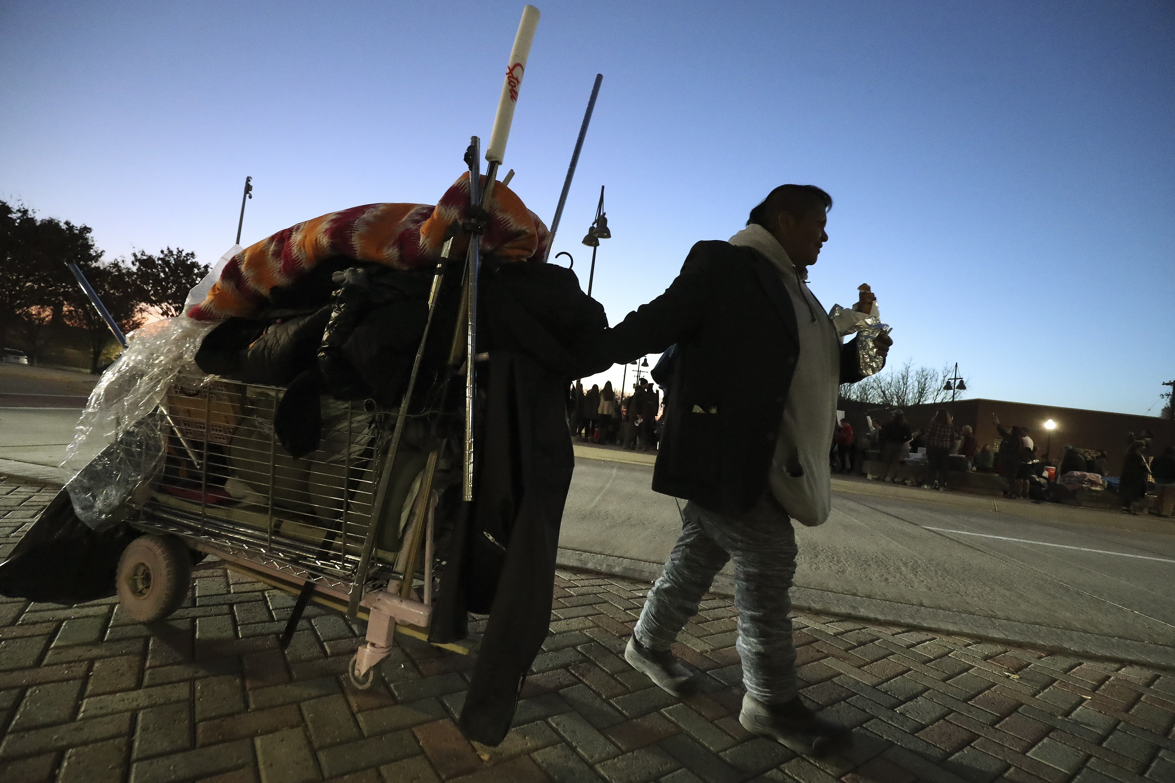 Terry Manyhides, who is homeless, pulls her possessions as protesters hold a rallyin Salt Lake City on Thursday, Nov. 7, 2019, to keep the Road Home open. The shelter is scheduled to close at the end of the month as thelast of three new homeless resource centers opens.