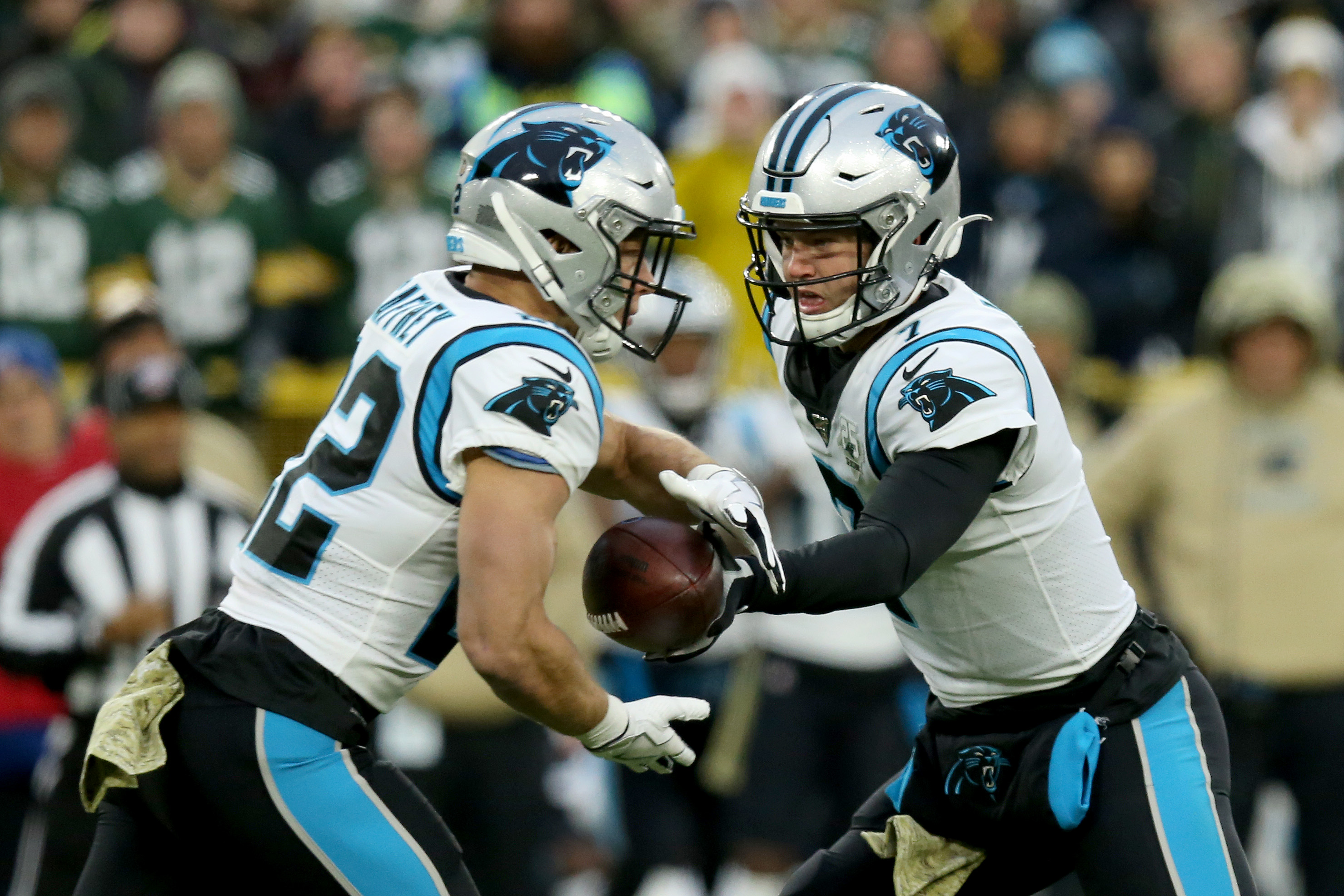 Kyle Allen of the Carolina Panthers hands the ball off to Christian McCaffrey against the Green Bay Packers during the first quarter in the game at Lambeau Field on November 10, 2019 in Green Bay, Wisconsin.