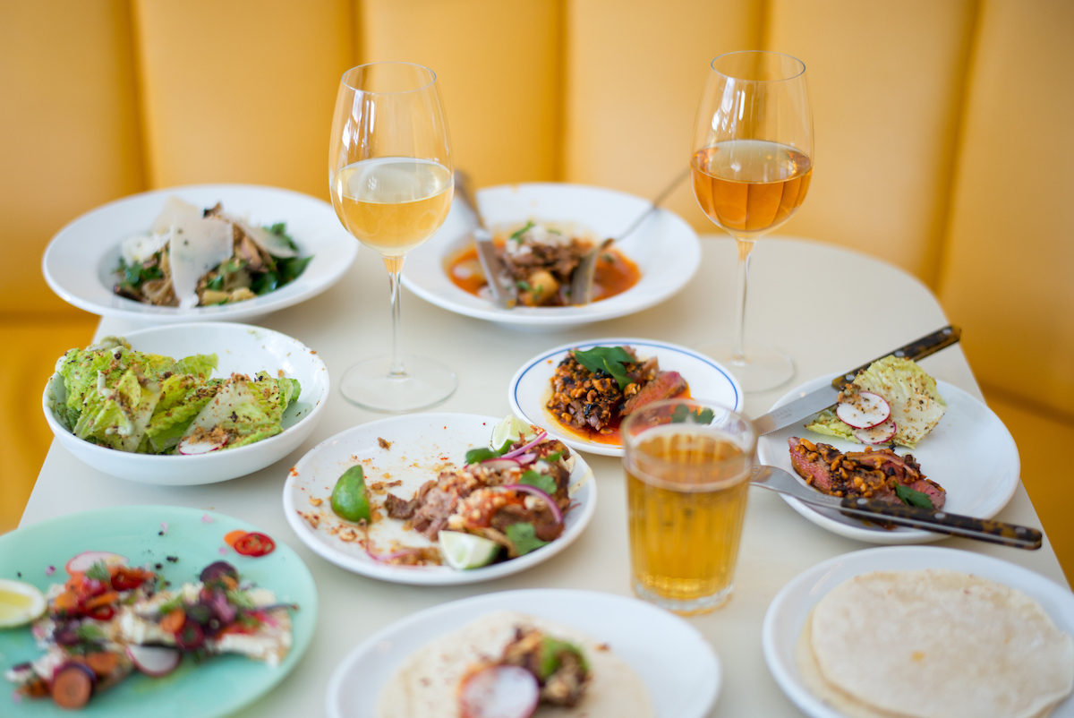 A table of dishes and wine at Lalo, the restaurant that preceded Lalito