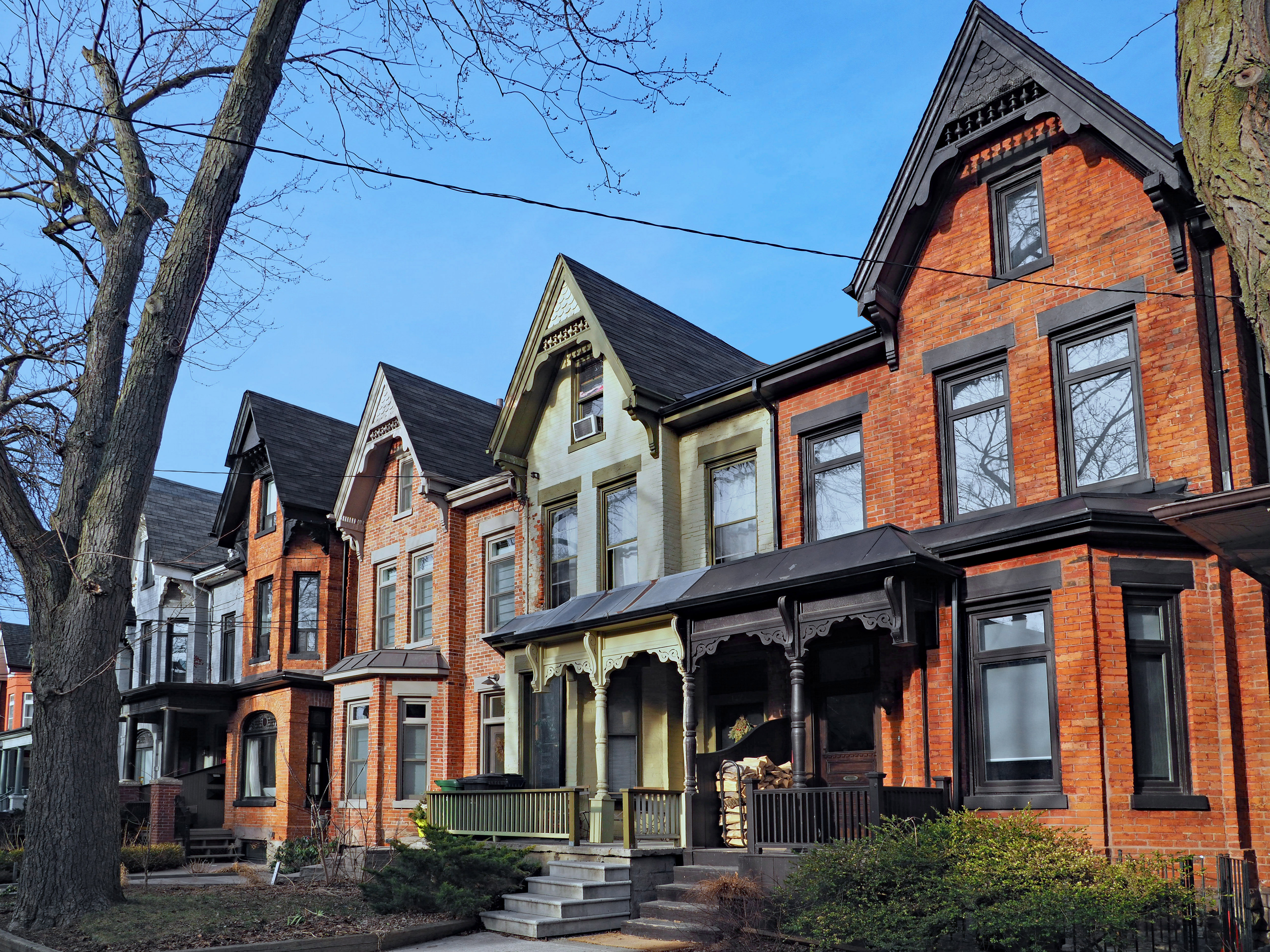 A row of brick houses with Victorian embellishments.
