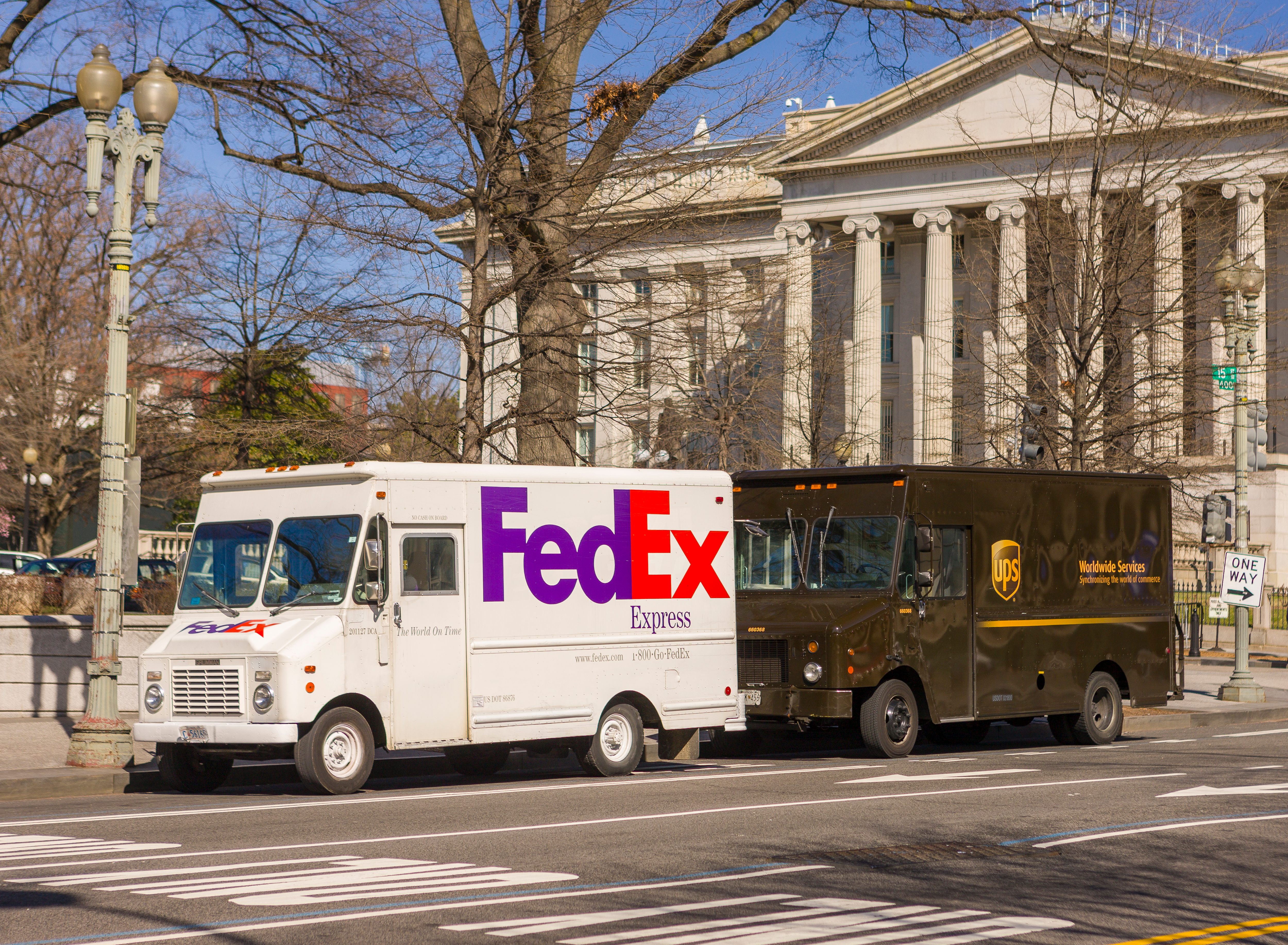 Two delivery trucks—one white, the other brown—are at rest outside of a classical building on a city street.