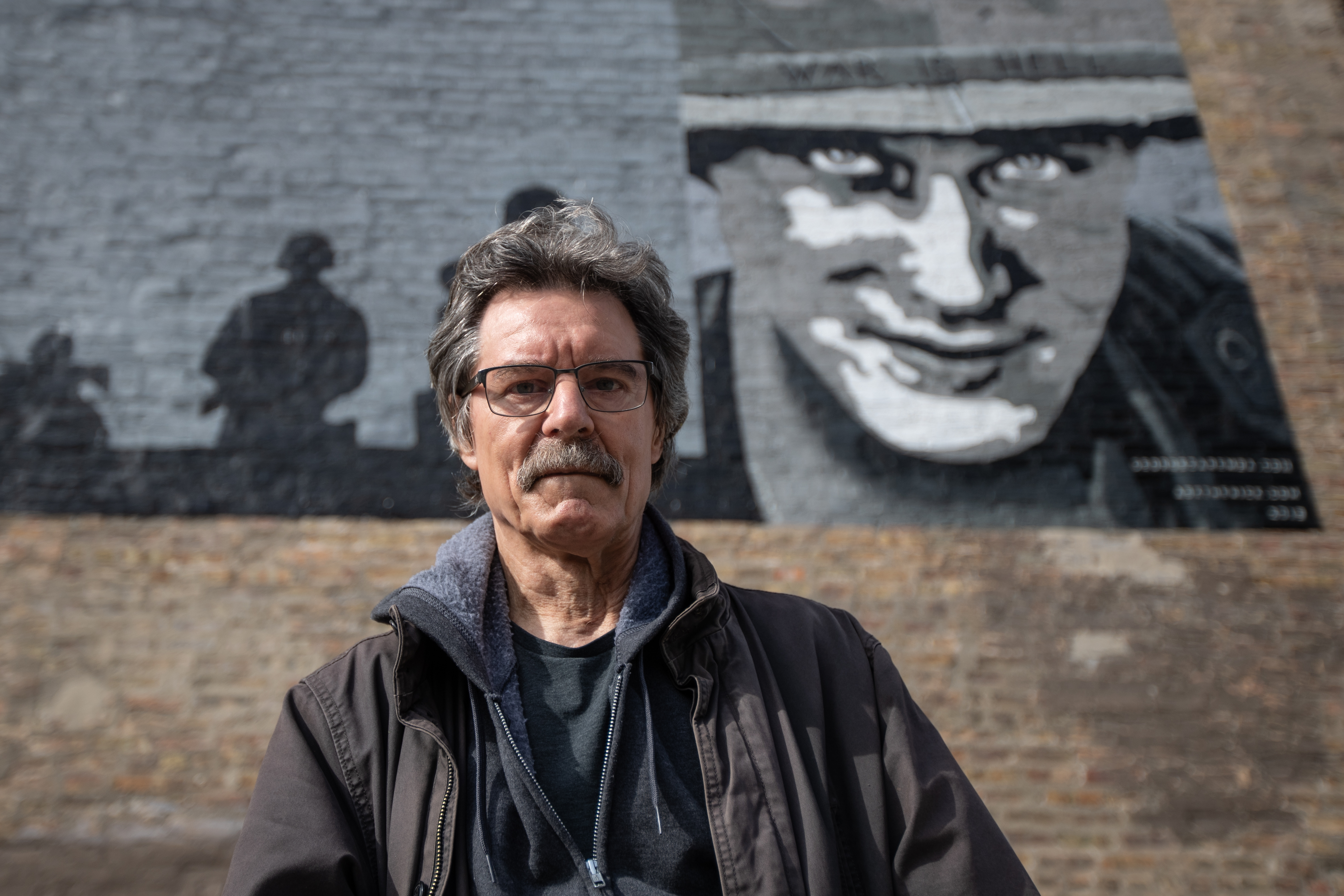 """George Zaremba in front of his mural """"WE REMEMBER"""" at North Sacramento Boulevard and West Carroll Avenue on the West Side."""