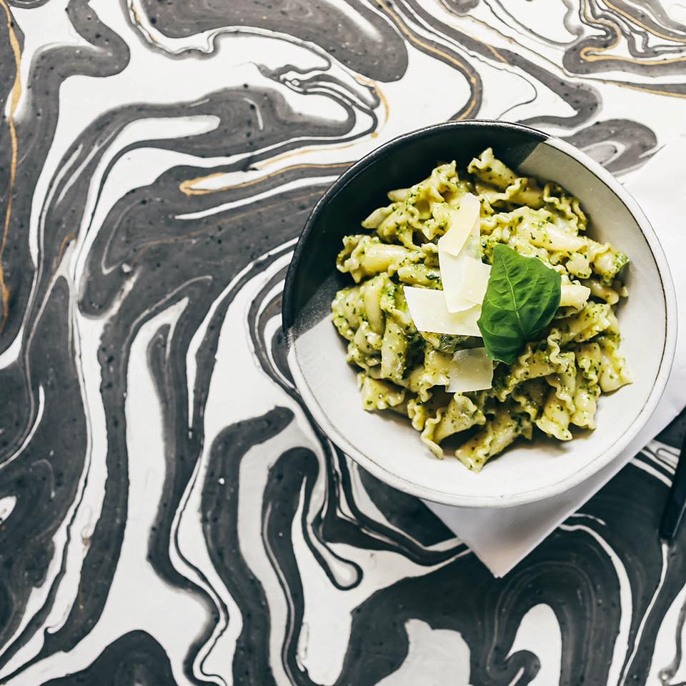 A bowl of pesto-topped pasta sits atop a black and white swirled table top