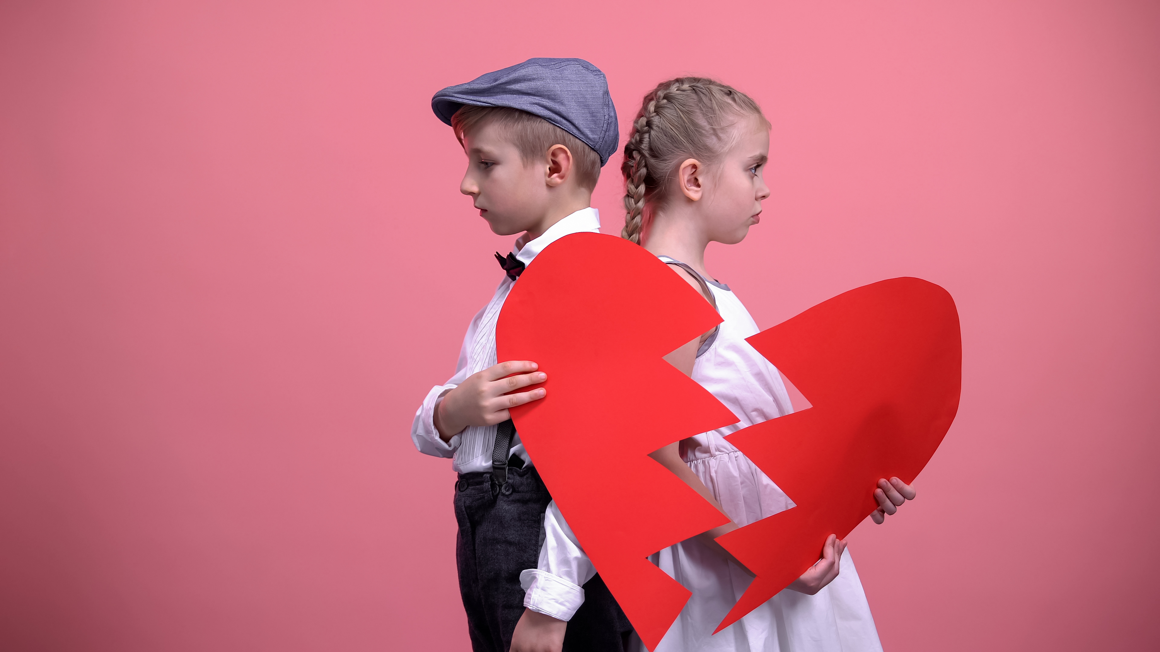 Sad child couple holding broken pieces of a red heart