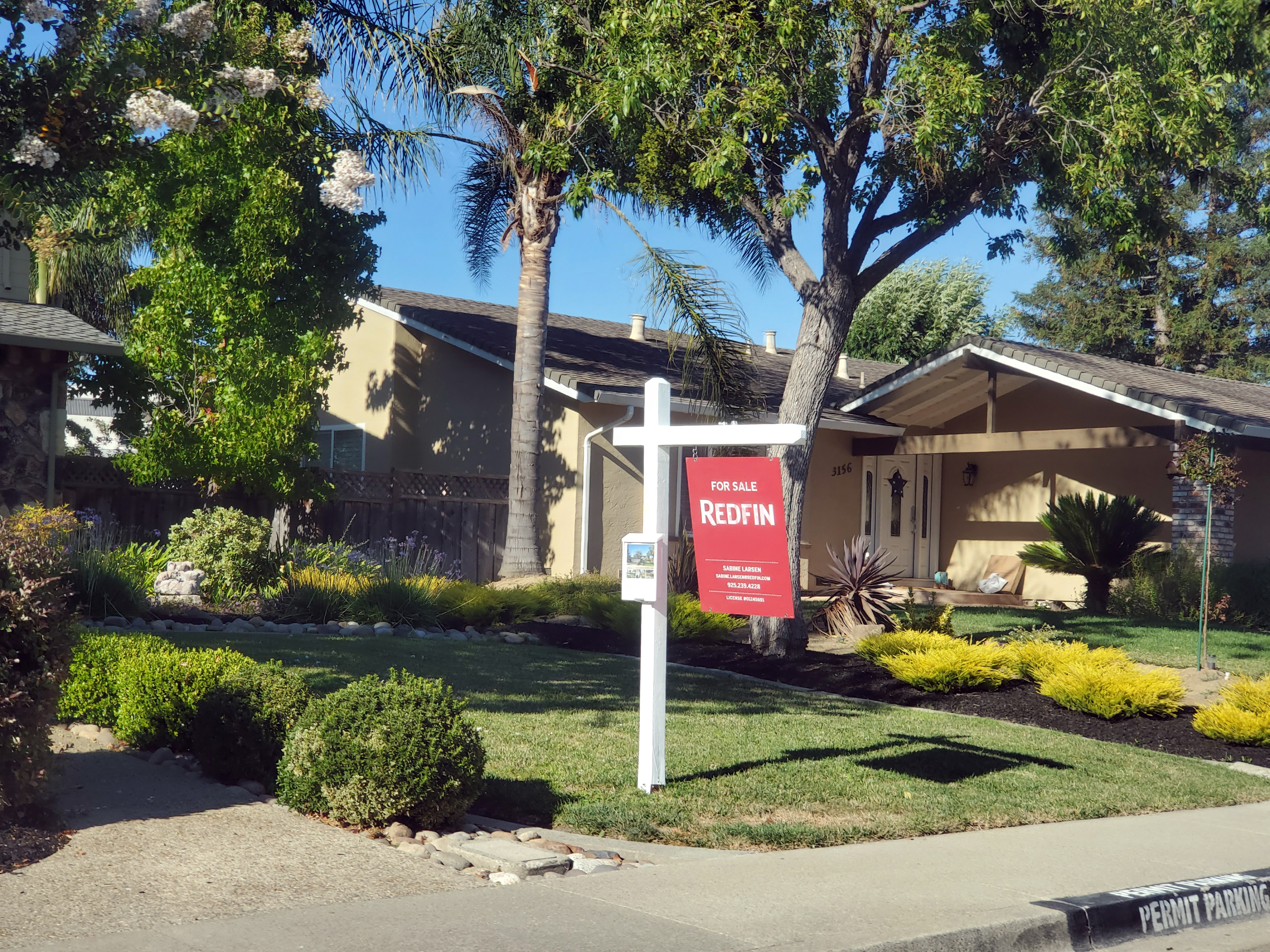 A house with a Redfin for-sale sign in front of it.