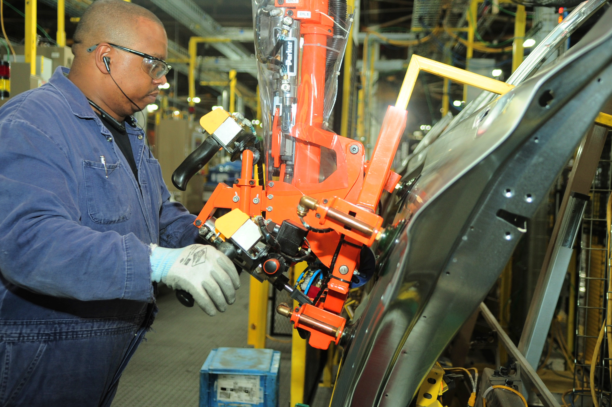 An assembly line worker uses suction cups to lift Explorer SUV doors into place at Ford's Chicago Assembly Plant on June 24, 2019.