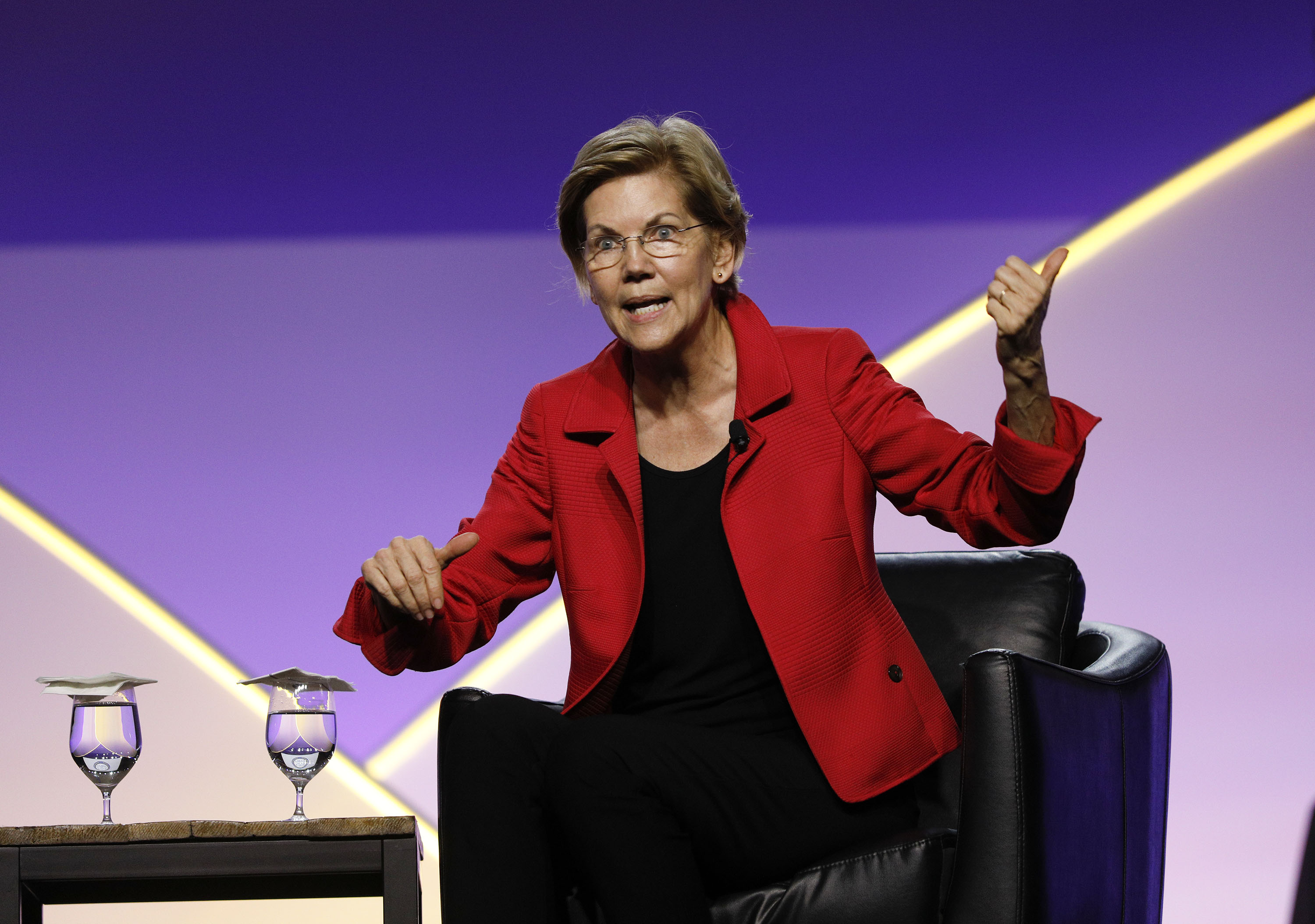 Sen. Elizabeth Warren seated onstage speaking to an audience.