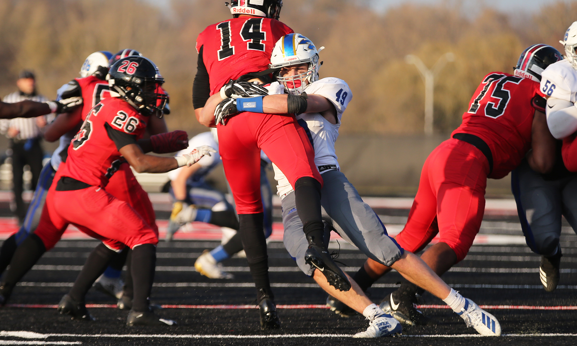 Warren's Seamus Mellican (49) puts a hit on Bolingbrook quarterback Devyn Suggs (14) as he releases the ball.