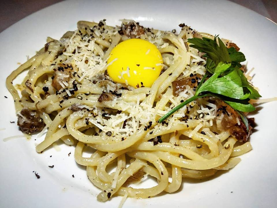 A plate of bucatini carbonara with visible flecks of black pepper, guanciale, pasta, and an egg yolk