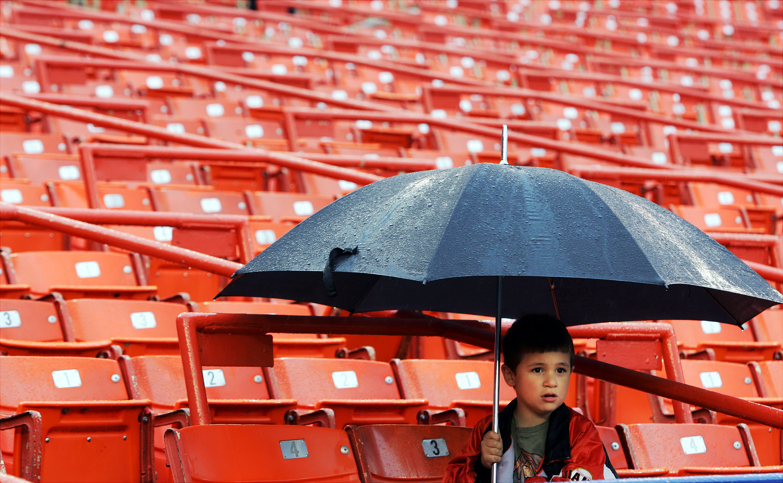 Gerardo Perez, 6, keeps himself dry with a very large umbrel