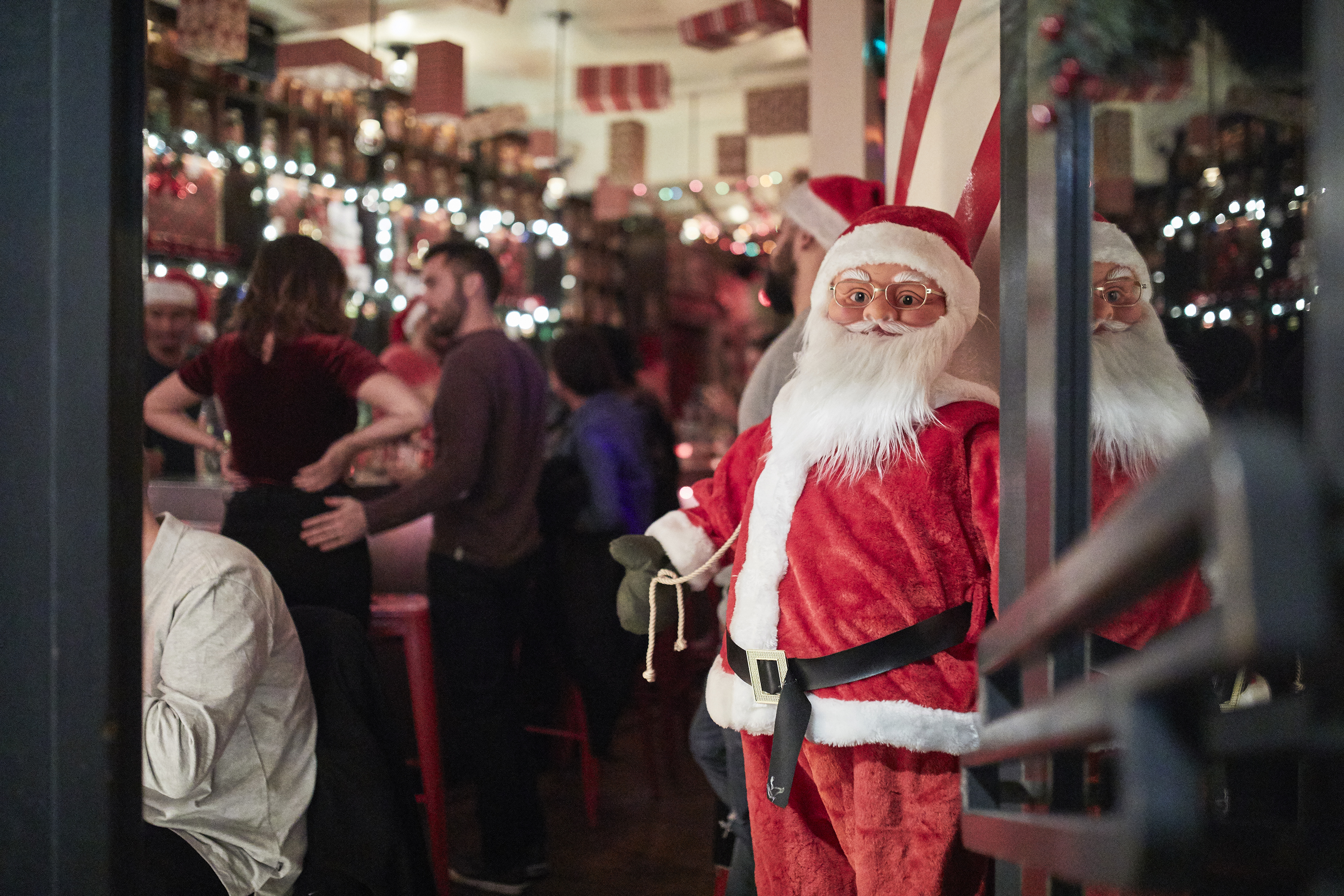 A Santa Claus figuring stands at the front of a bar, where people are standing in a space decorated for the Christmas holidays.