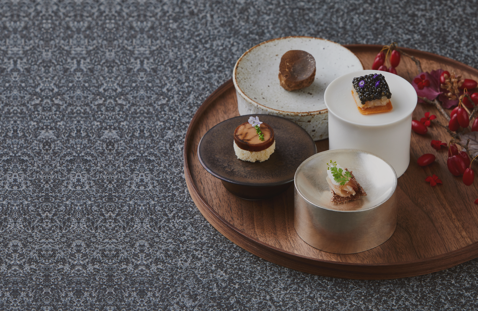 A wooden tray holding four small dishes each with a composed bite of food