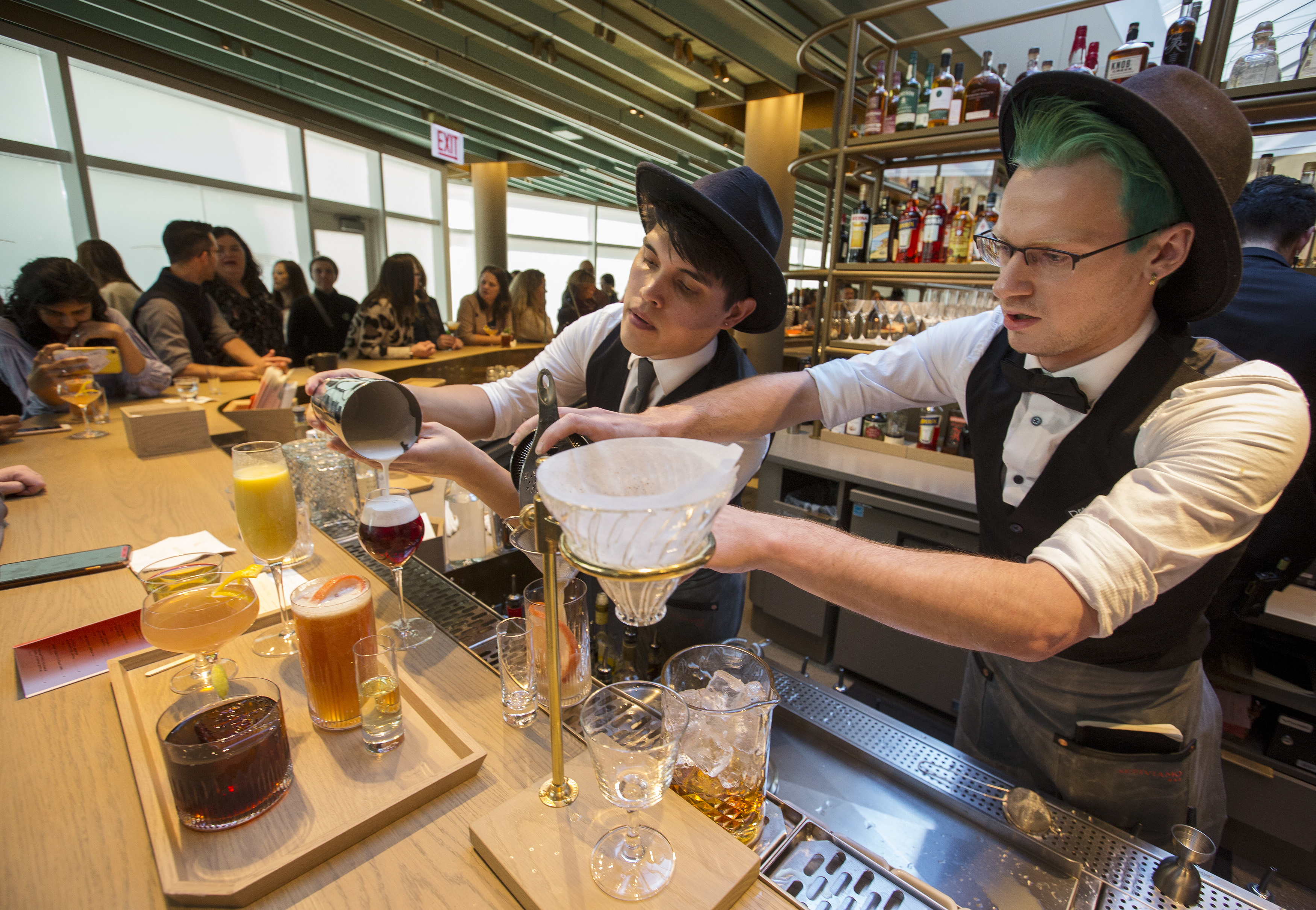 Two bartenders work on drinks behind a bar with diners in the background.