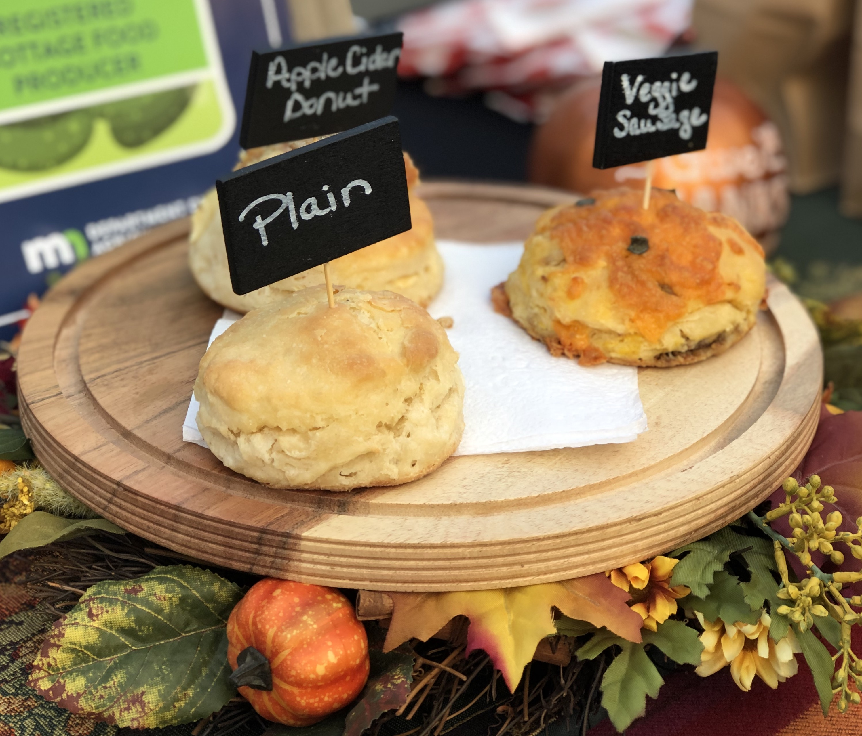 Three biscuits on a stand: plain, apple cider doughnut, and veggie and sausage