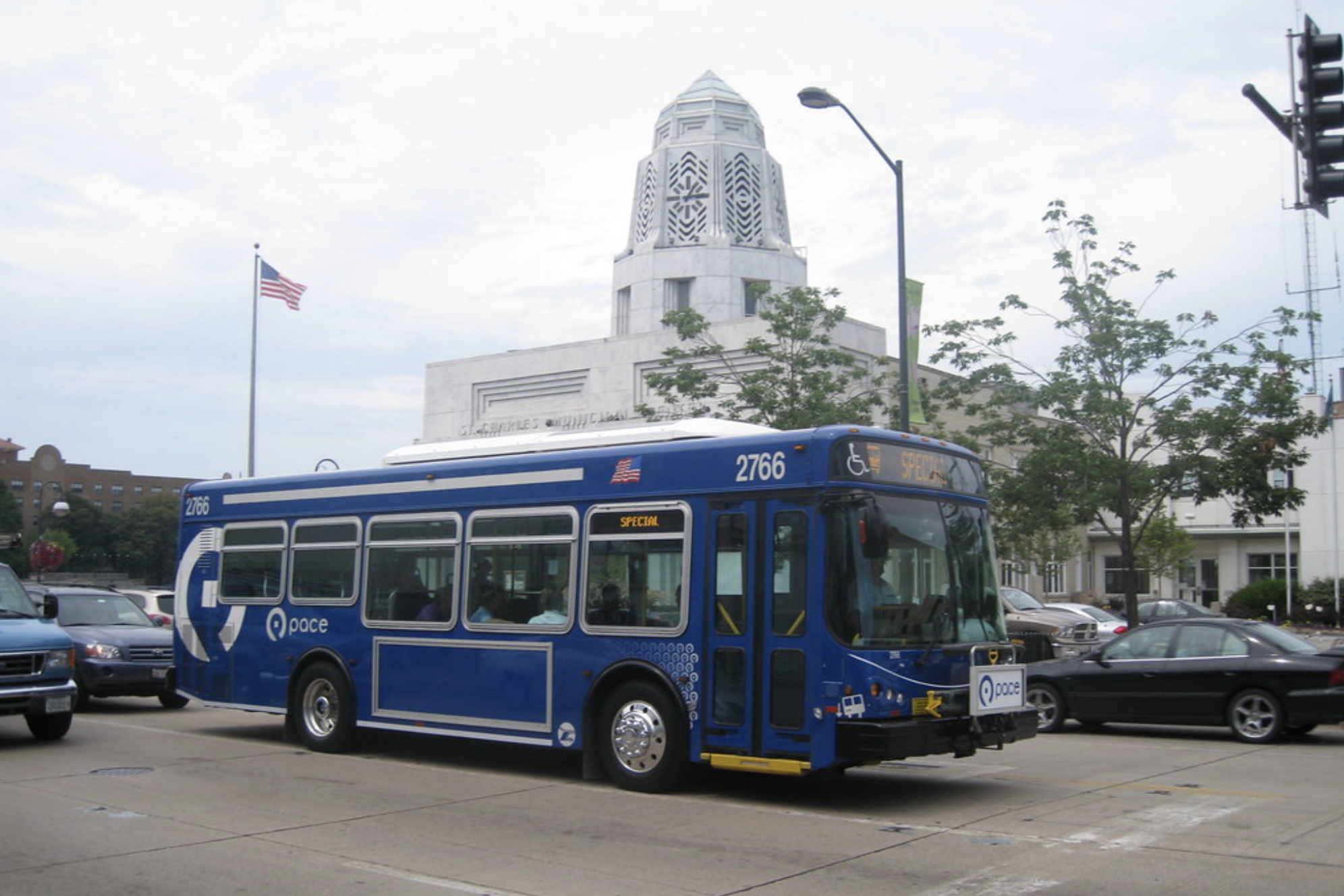 An image of a blue city bus with a domed building in the background.