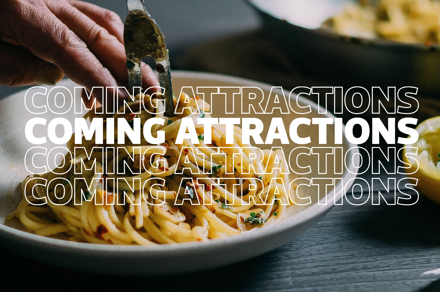 """Fingers push and herb-filled pile of noodles off a two pronged fork into a white bowl. The words """"Coming Attractions"""" is written several times across the photo."""