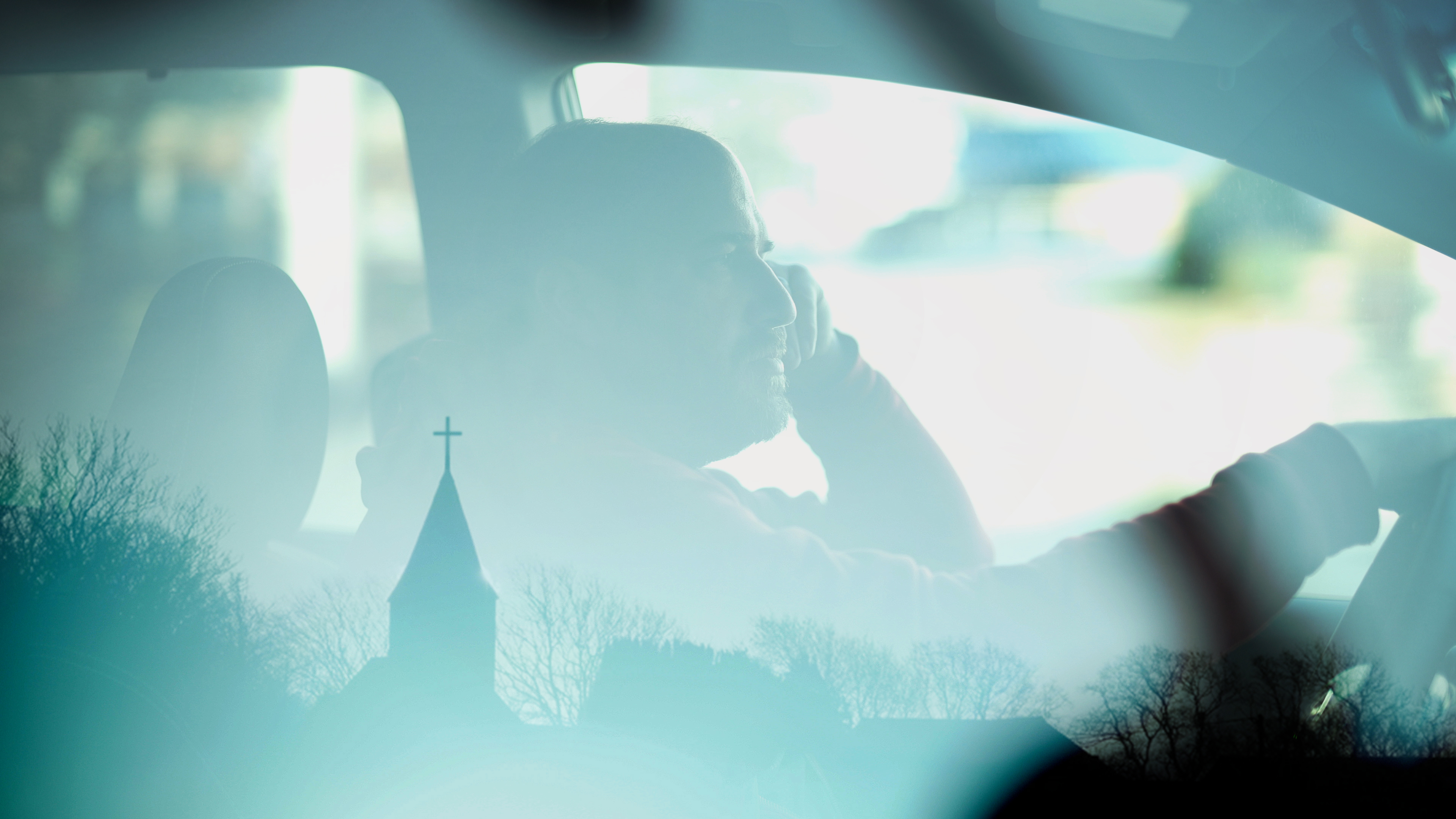Musician David Bazan sitting in his car in a still from Strange Negotiations.