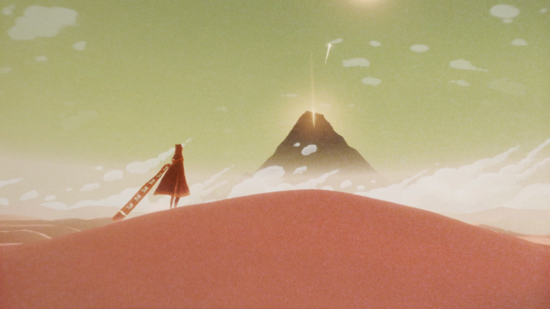 Video game character in the game Journey stands on a pink sand dune, looking at a glowing mountain top in the distance.