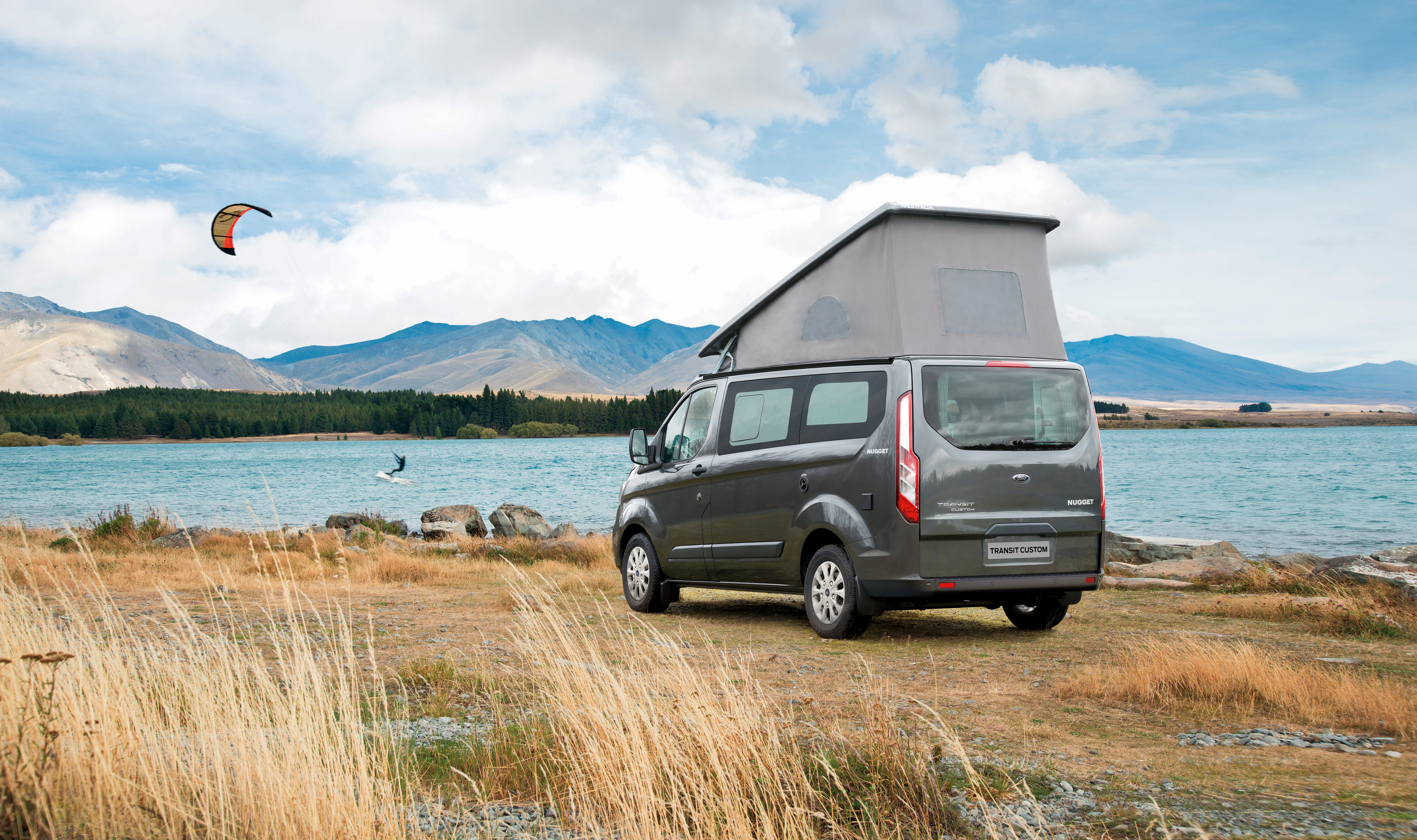 A gray pop-top camper van with its roof popped sits in a field next to a mountainous lake. There is a kite boarder on the lake.