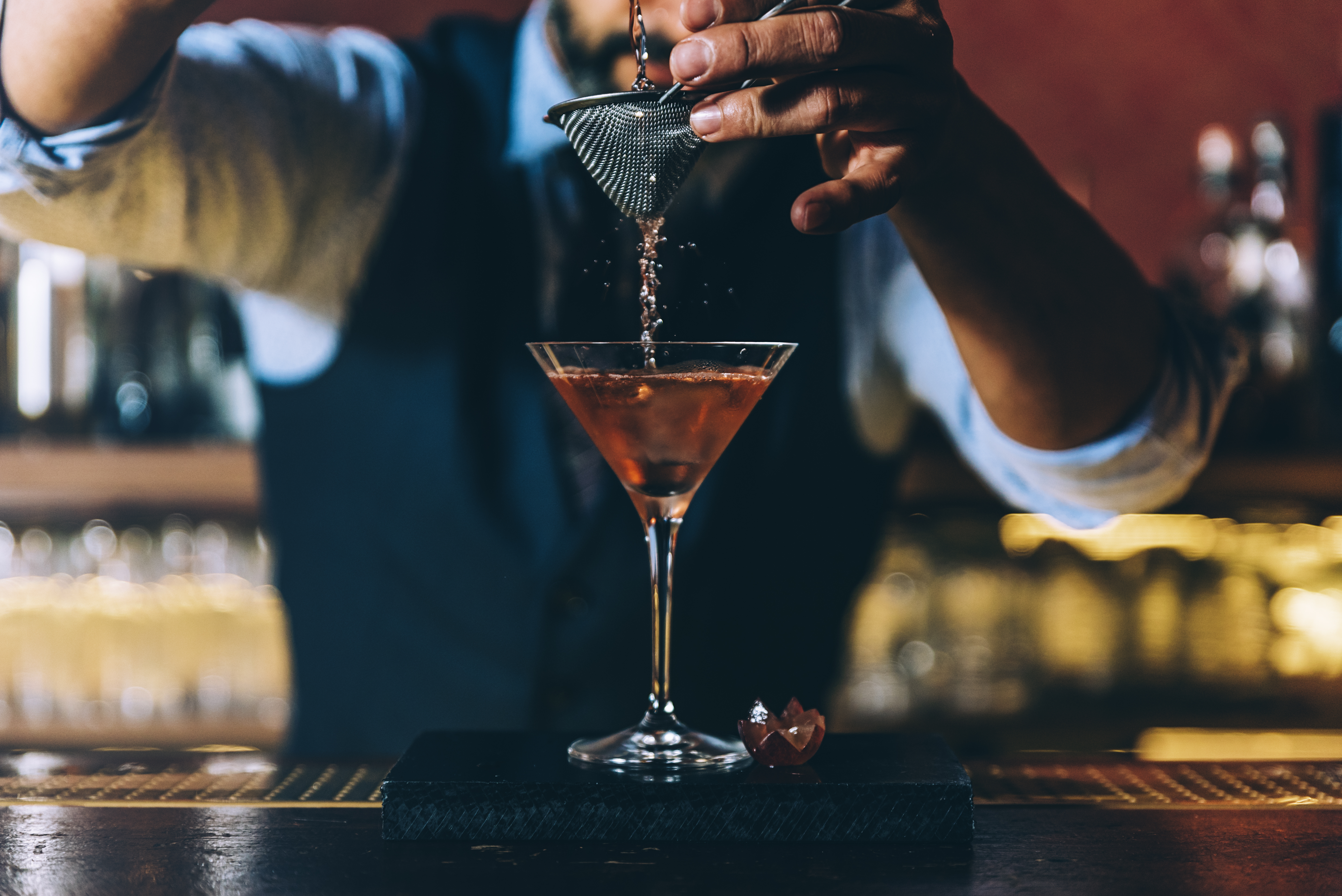 A bartender pouring a cocktail.