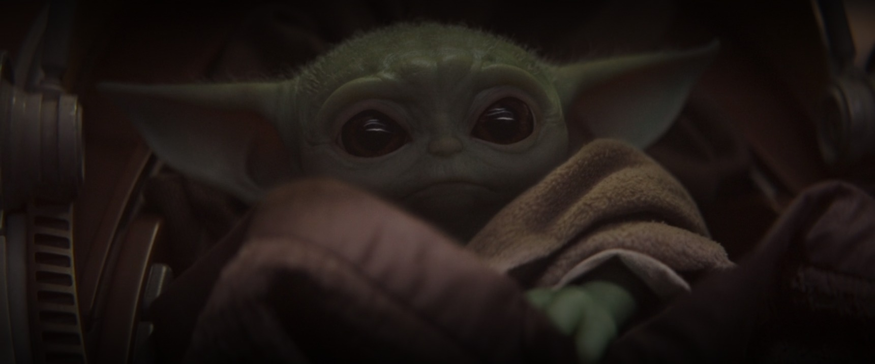 A little baby from Yoda's species lays in a space crib in The Mandalorian