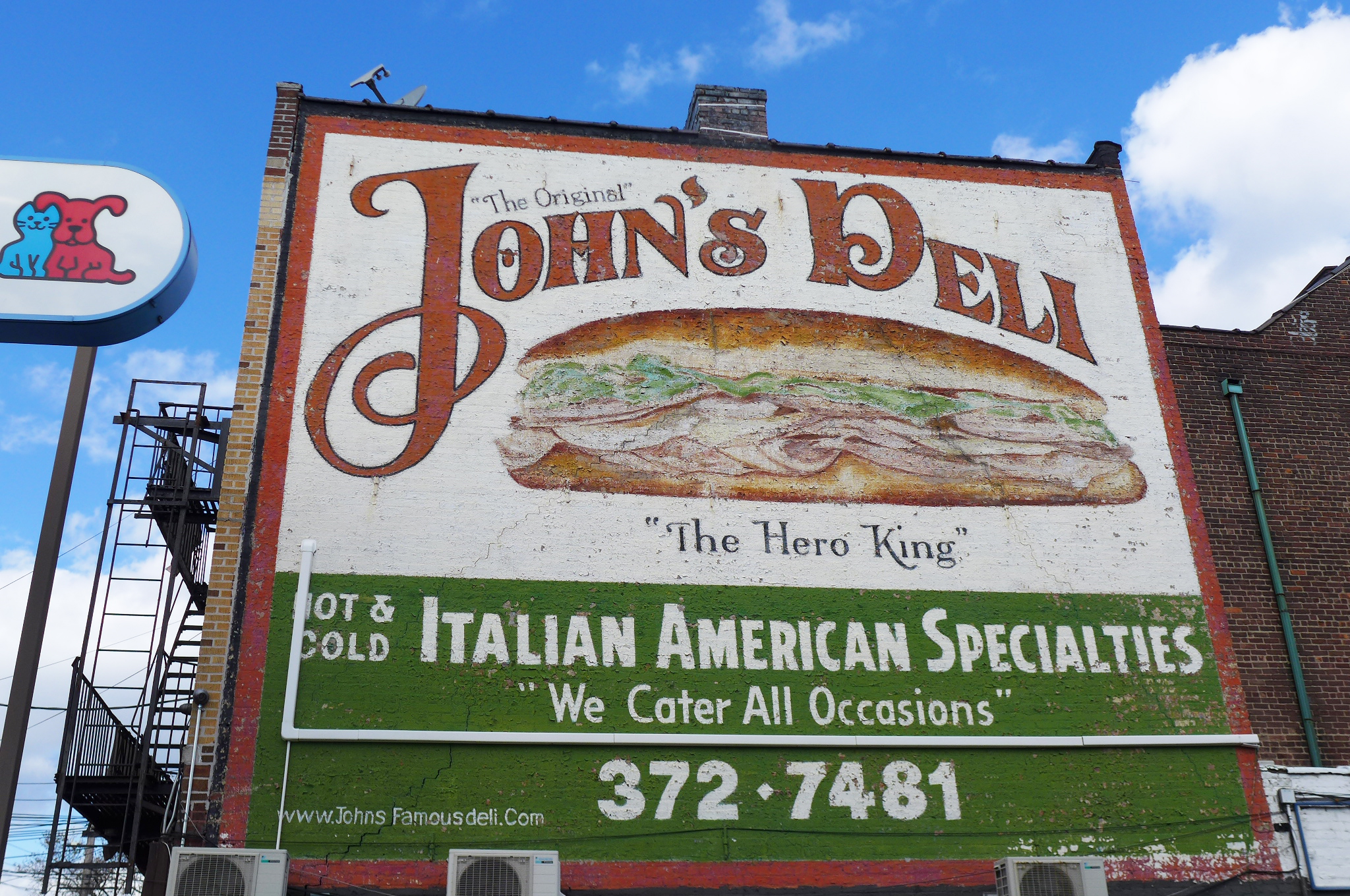 A sign painted on the entire side of the building reads John's Deli.